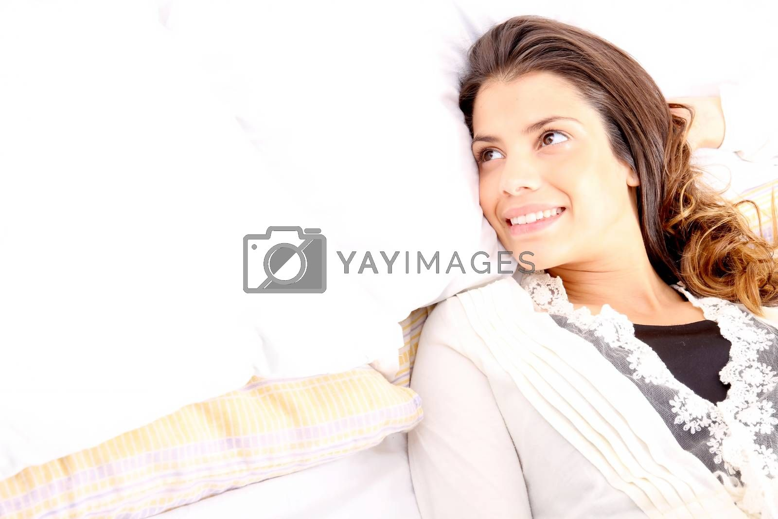 A young girl laying in bed and smiling