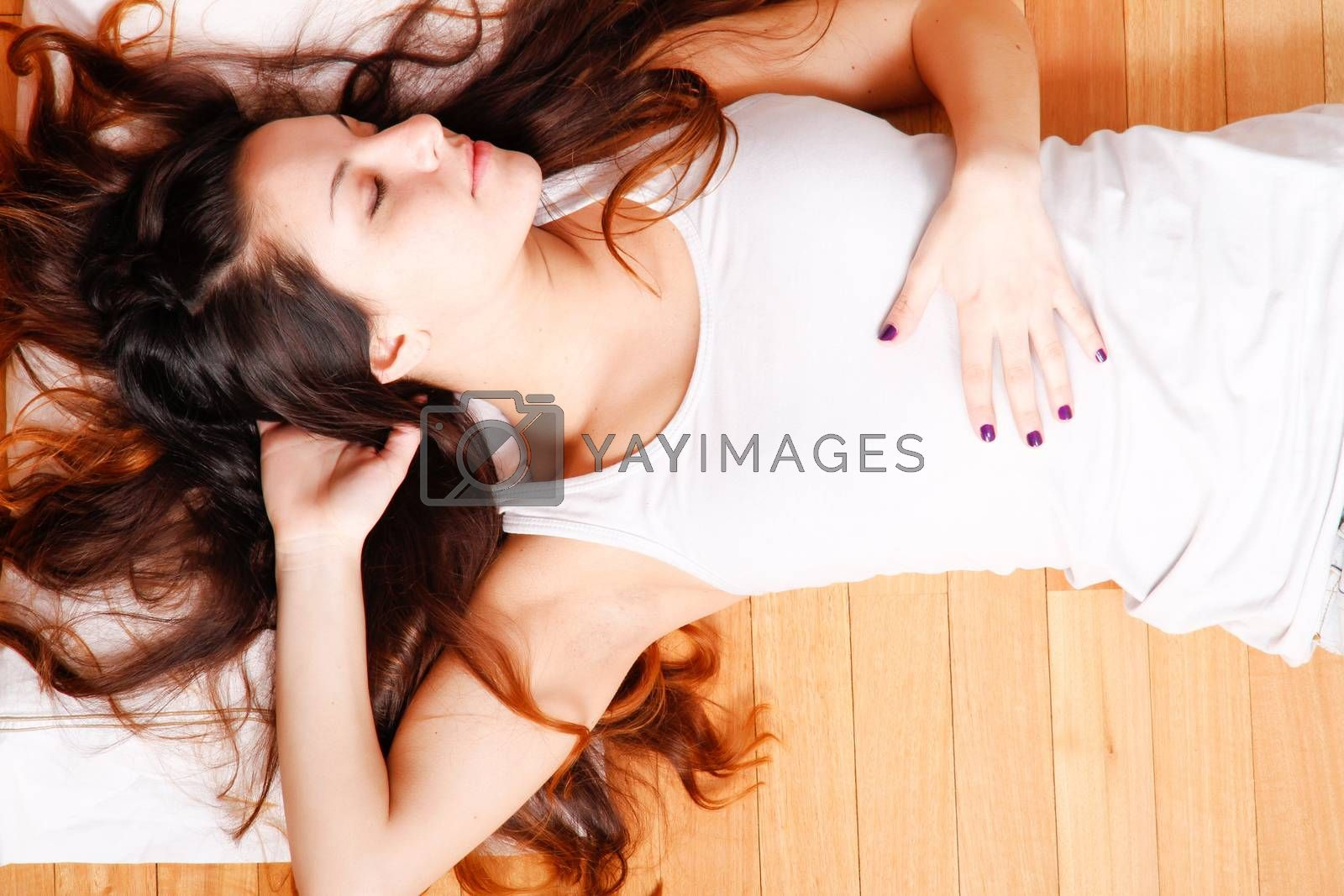 A young hispanic girl relaxing on the floor.