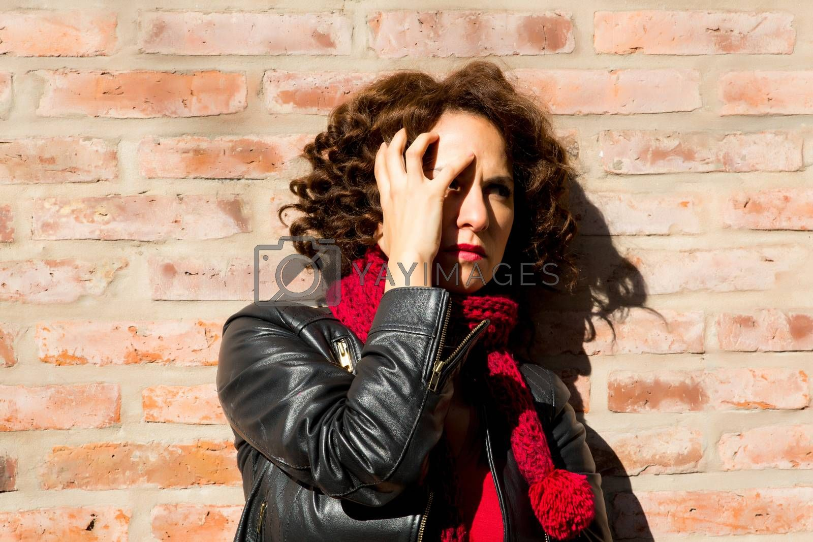 Worried woman standing at brick wall on the street.