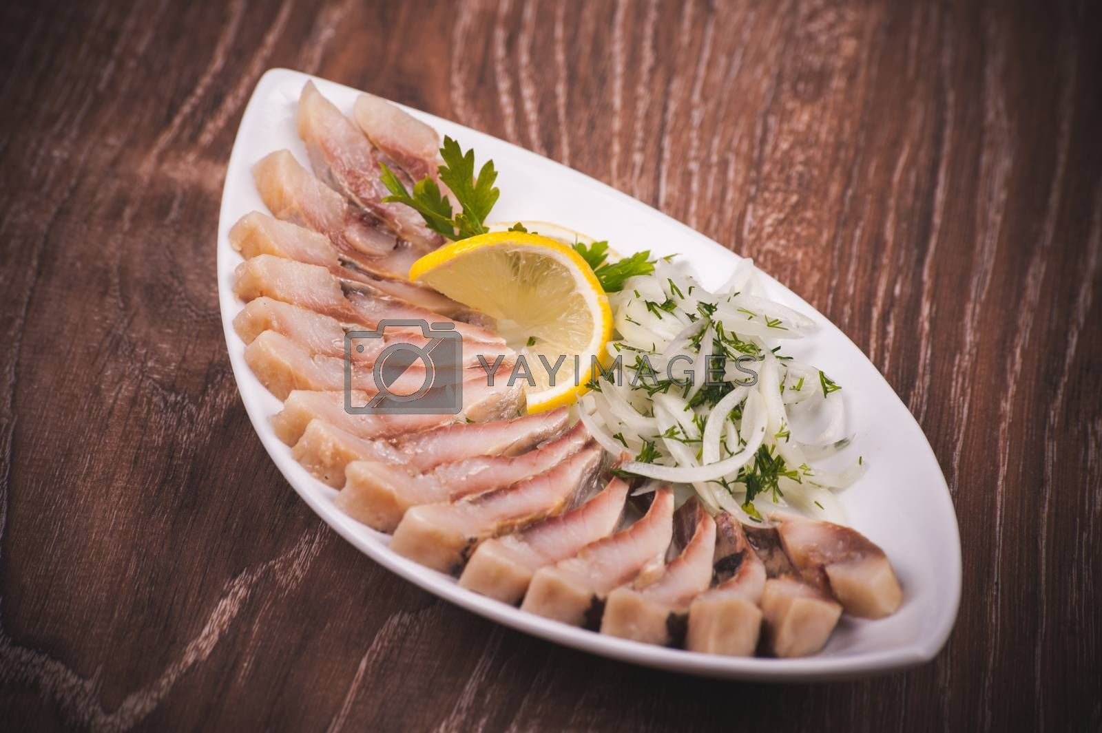 herring fish with marinated onion on white plate