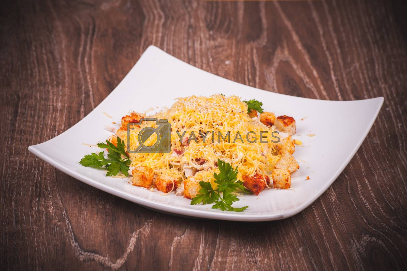 salad with bacon, crouton and cheese on white plate