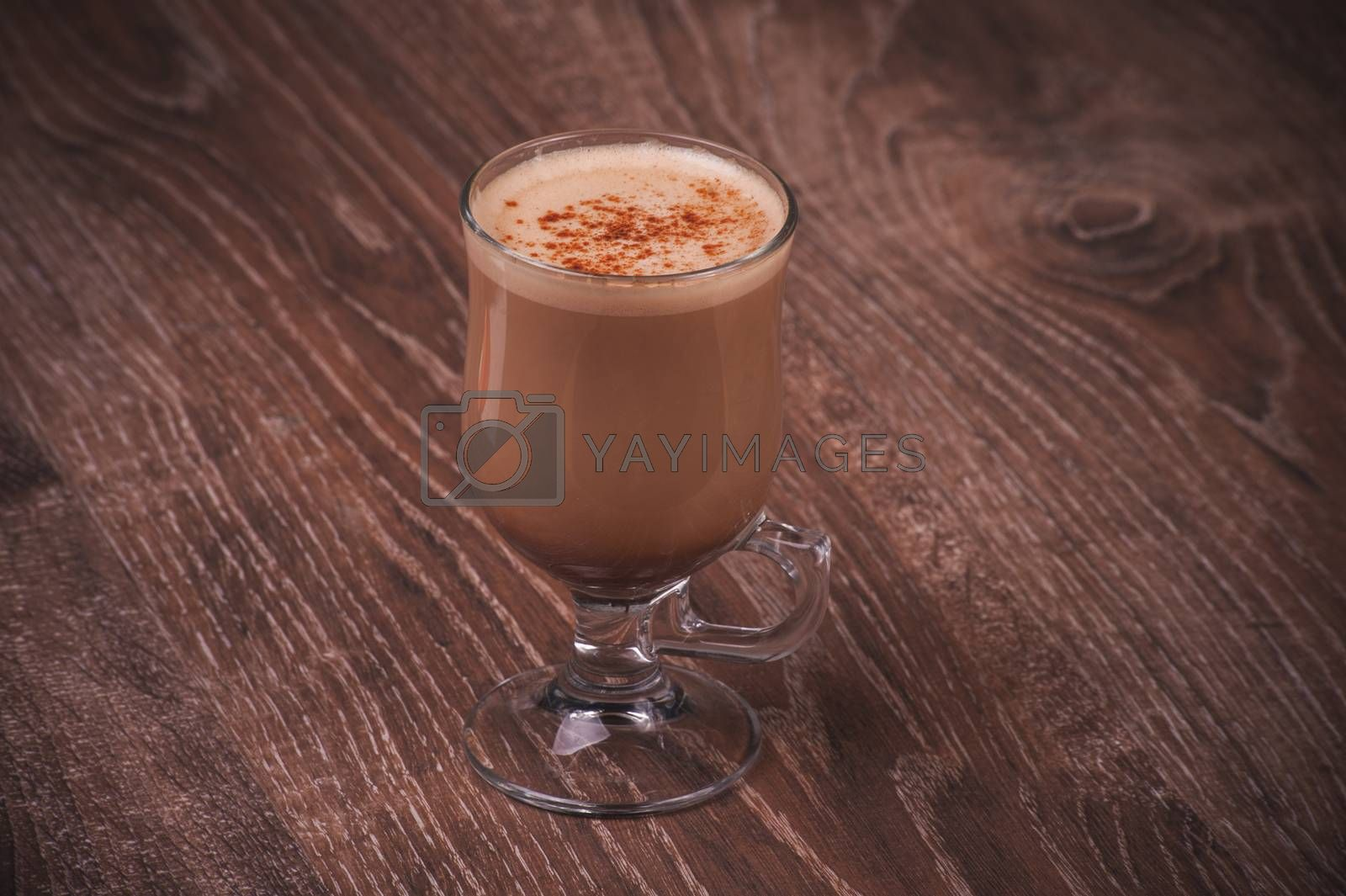 hot cacao drink in glass with milk foam