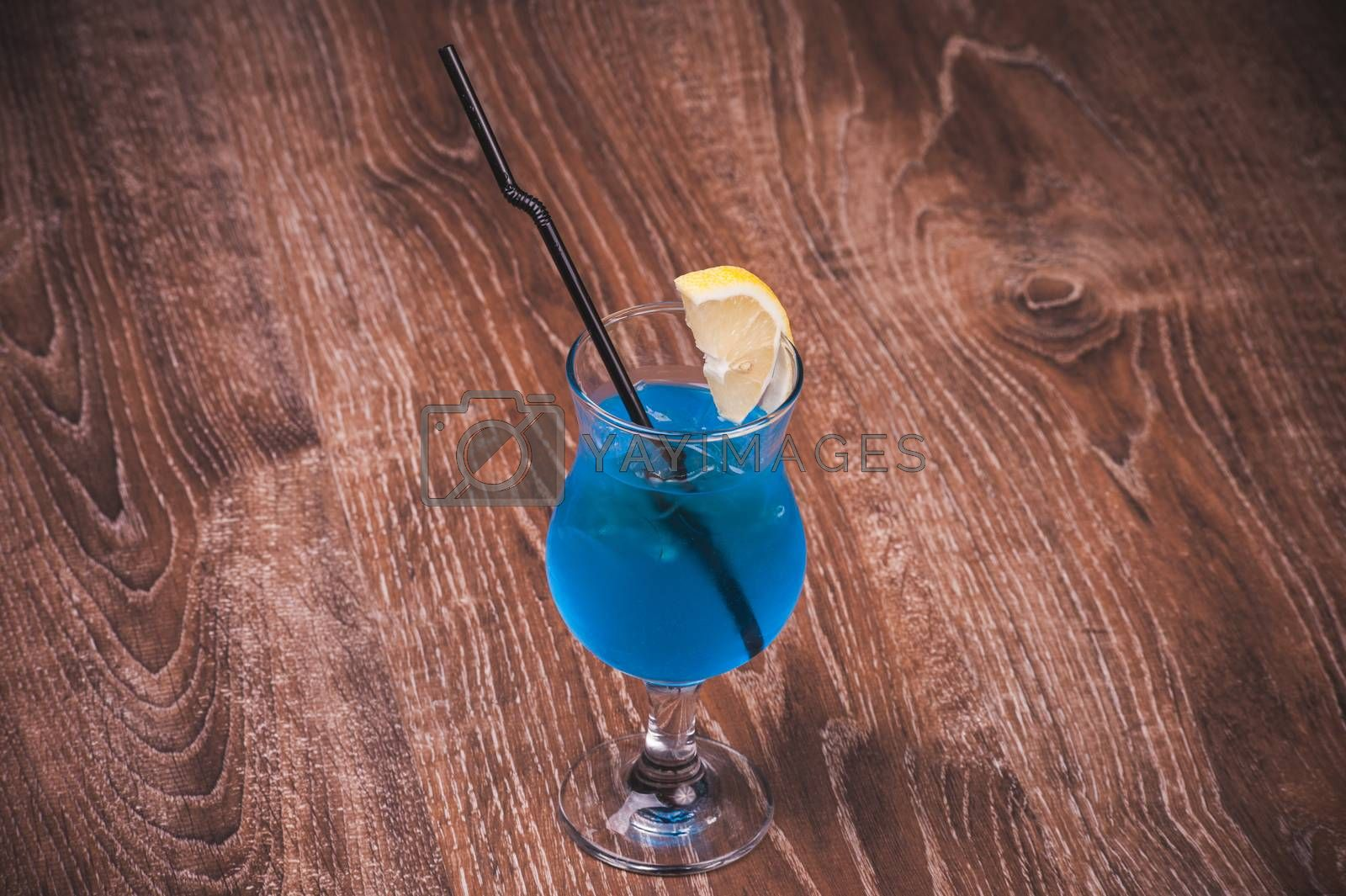 blue alcohol cocktail in high glass with straw