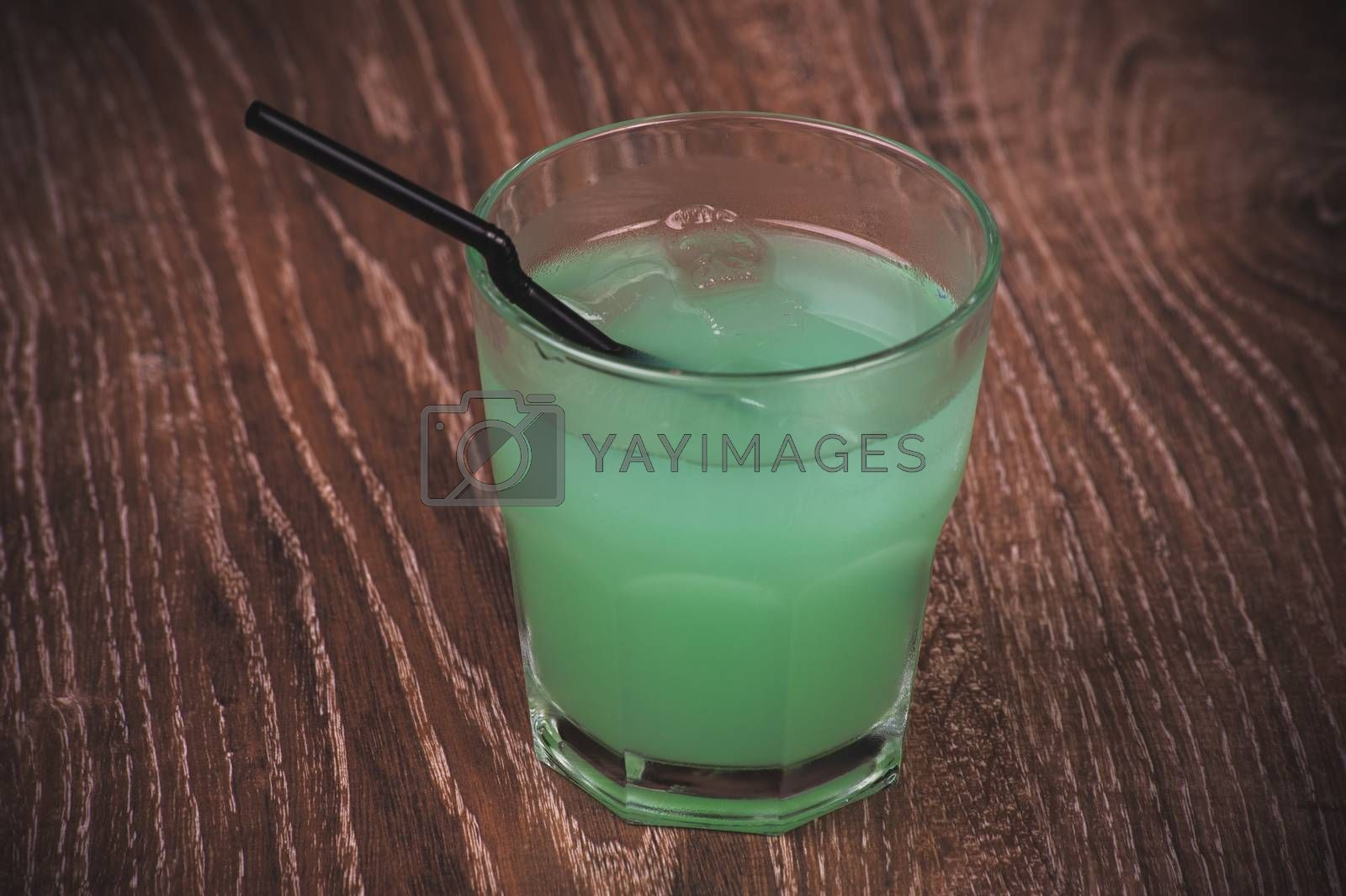 blue alcohol cocktail in glass with straw