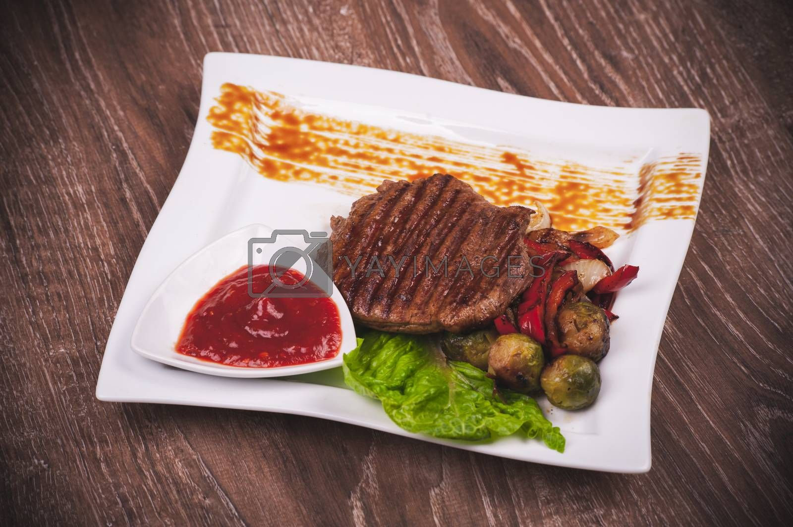 Grilled fillet of beef with vegetables on white plate