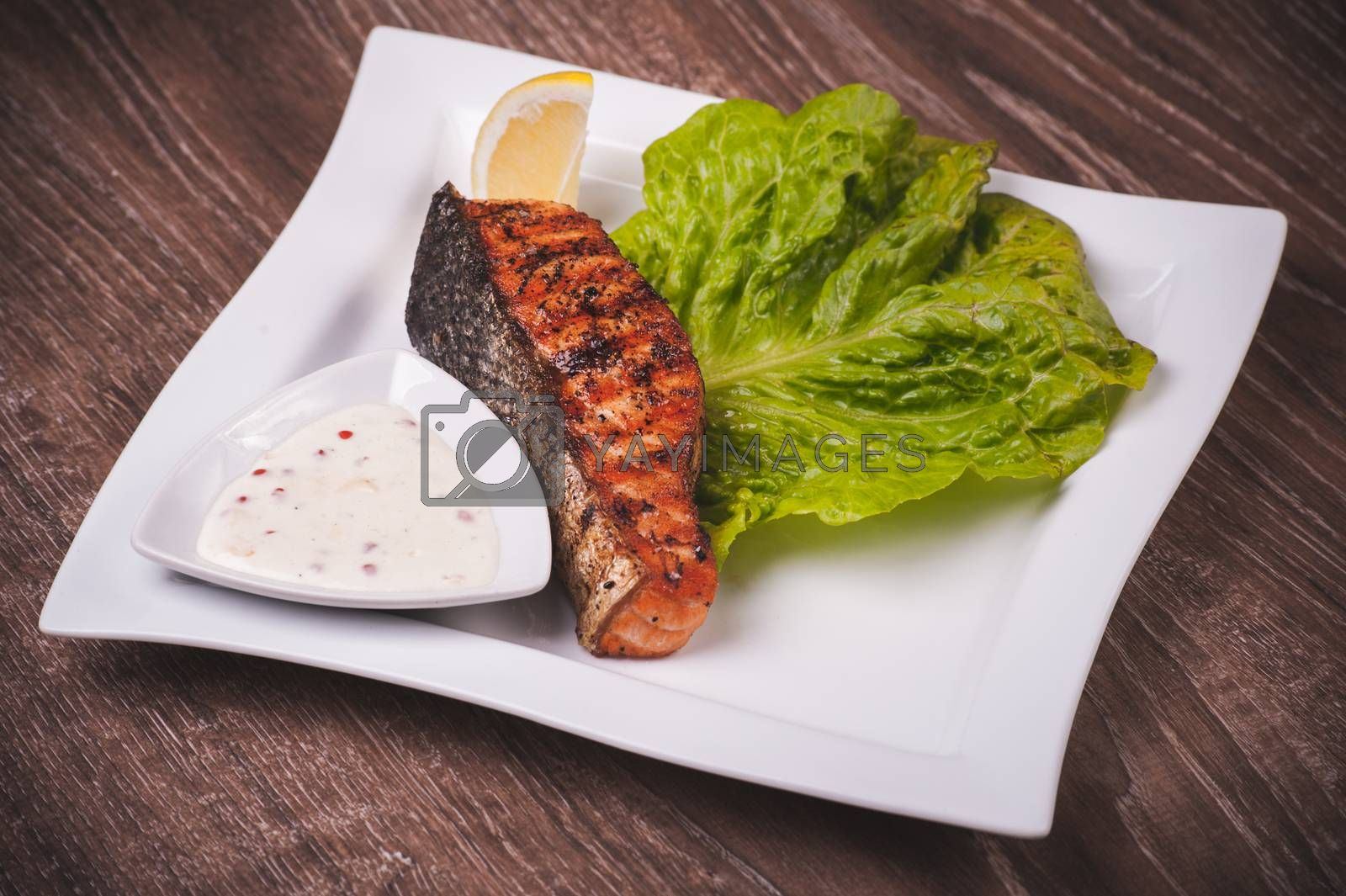 Grilled salmon with tartar sauce on white plate