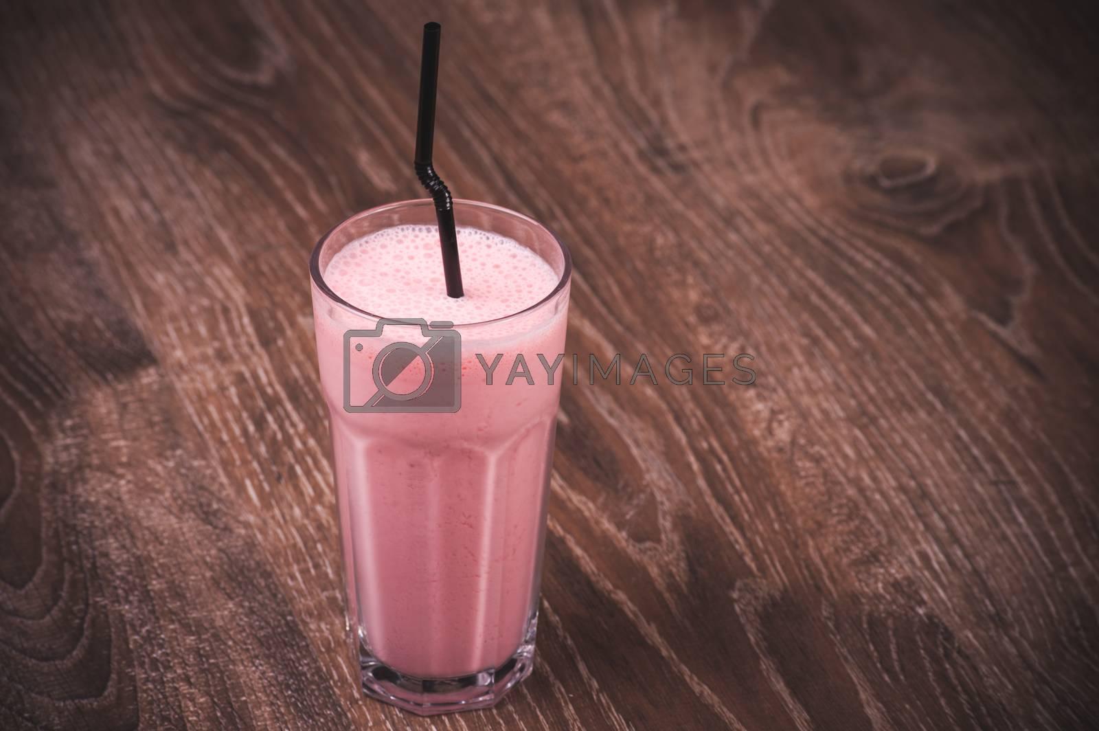 strawberry milkshake with straw in high glass