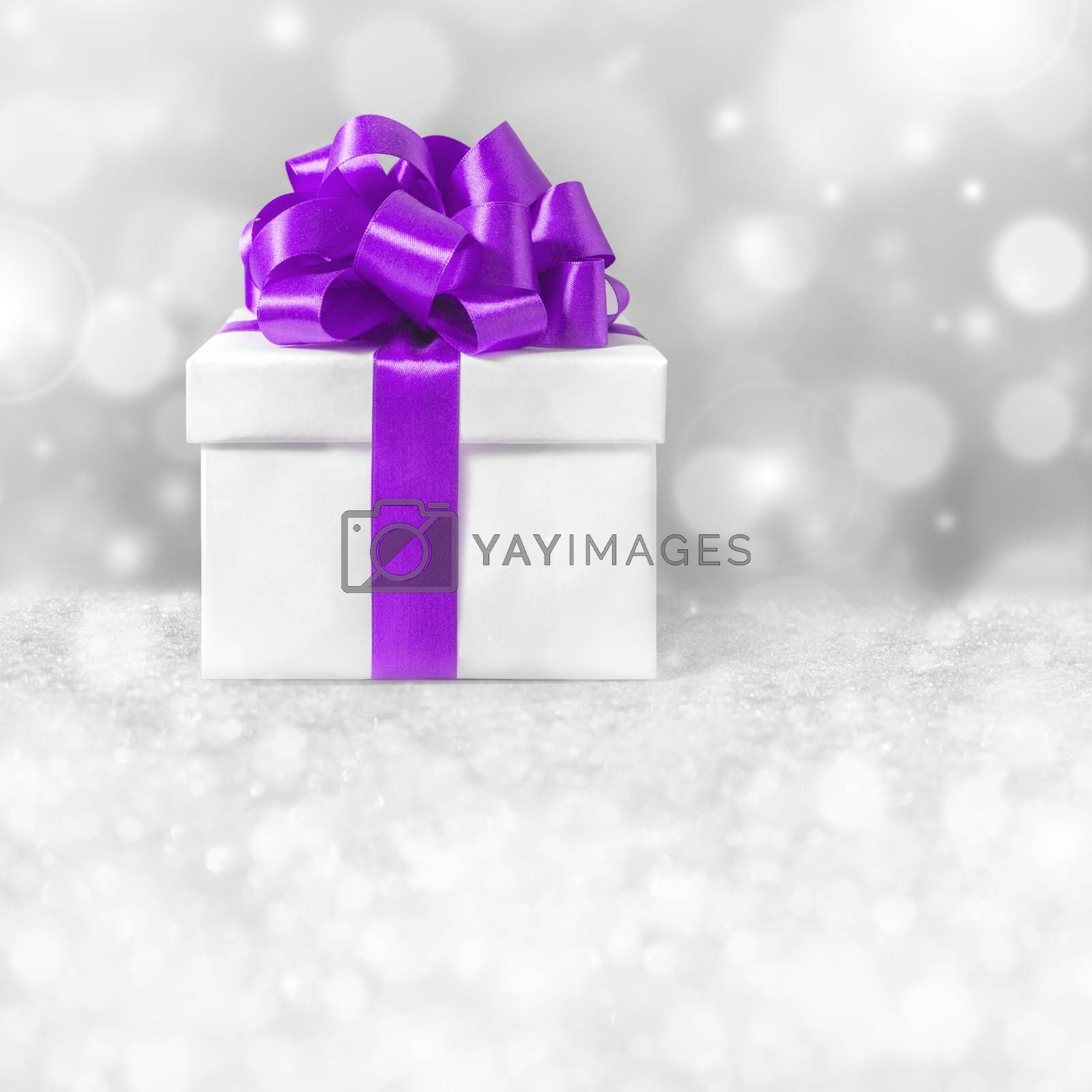 White gift box with purple ribbon bow,