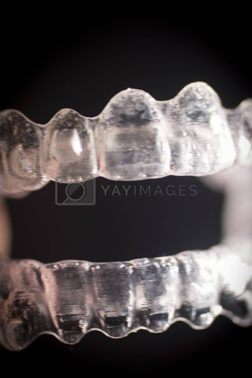 Close up macro photo of invisible transparent plastic dental brackets set against black studio background. Artistic color digital photo with shallow depth of focus.