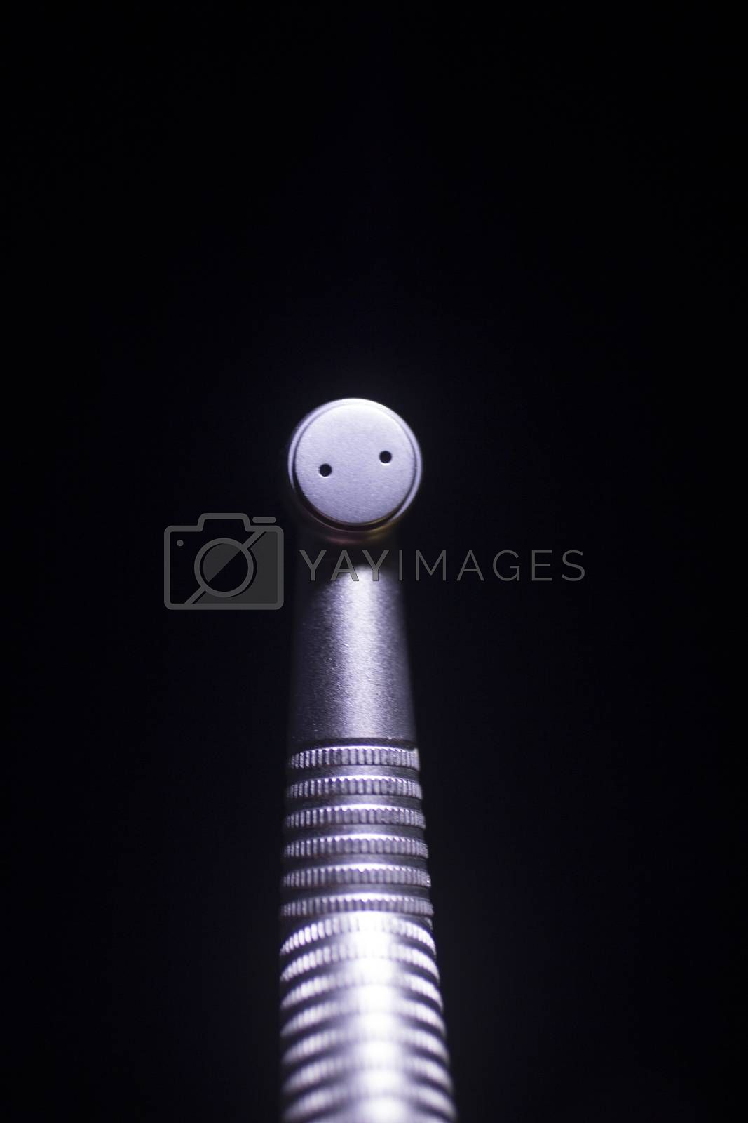 Rectangular vertical color close-up macro digital photo of dentists instrumentation dental tooth spray head against plain black studio background.