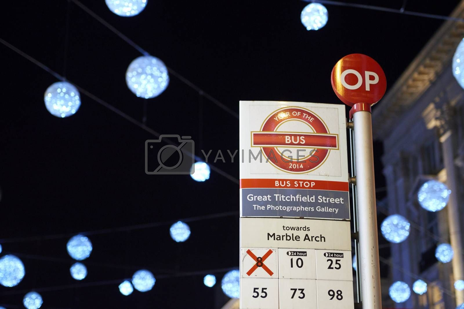 LONDON, UK - DECEMBER 20: Nighttime shot of London bus stop with Christmas lights in the background. December 20, 2014 in London.