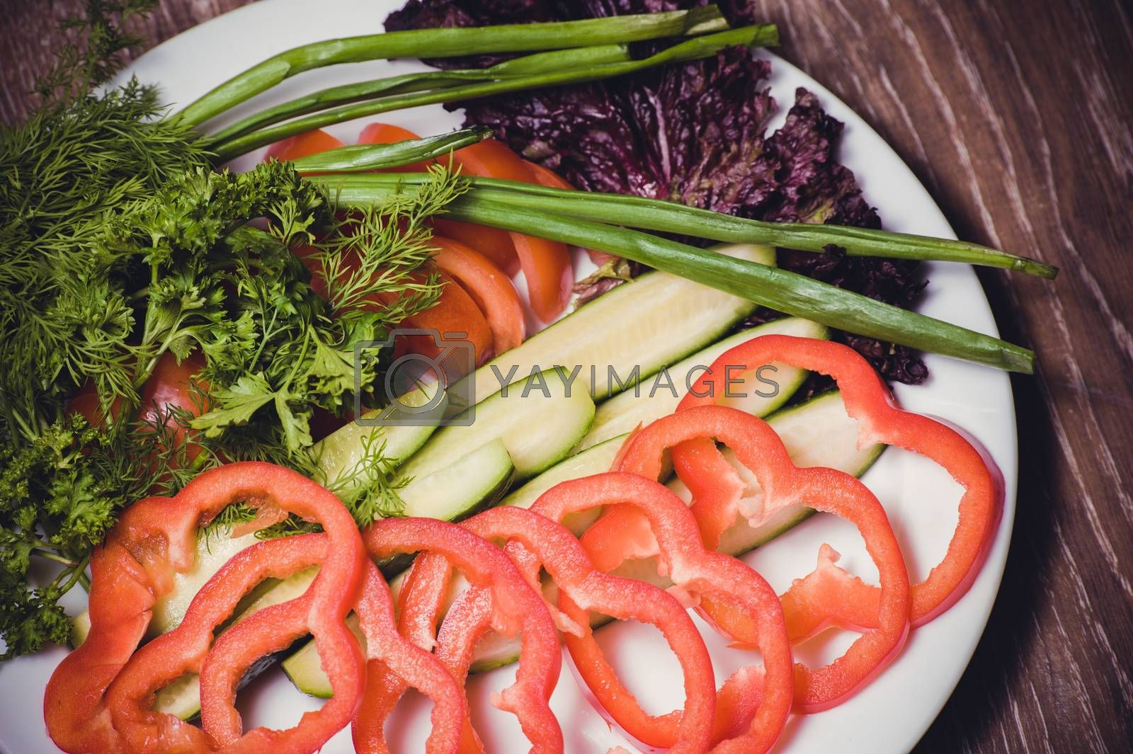 cut tomato, cucumber and bell pepper, on white plate