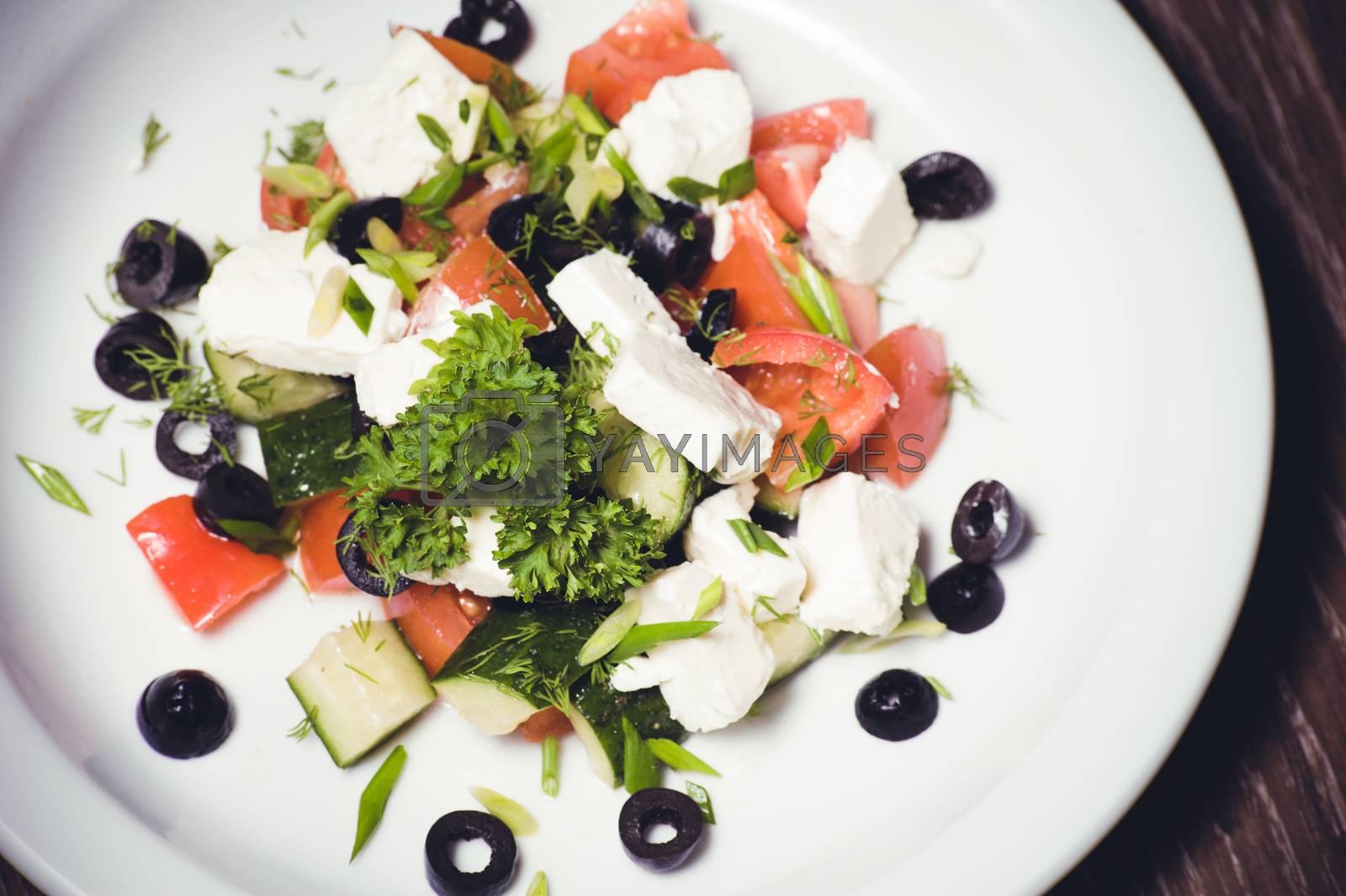 vegetarian greek salad served on white plate