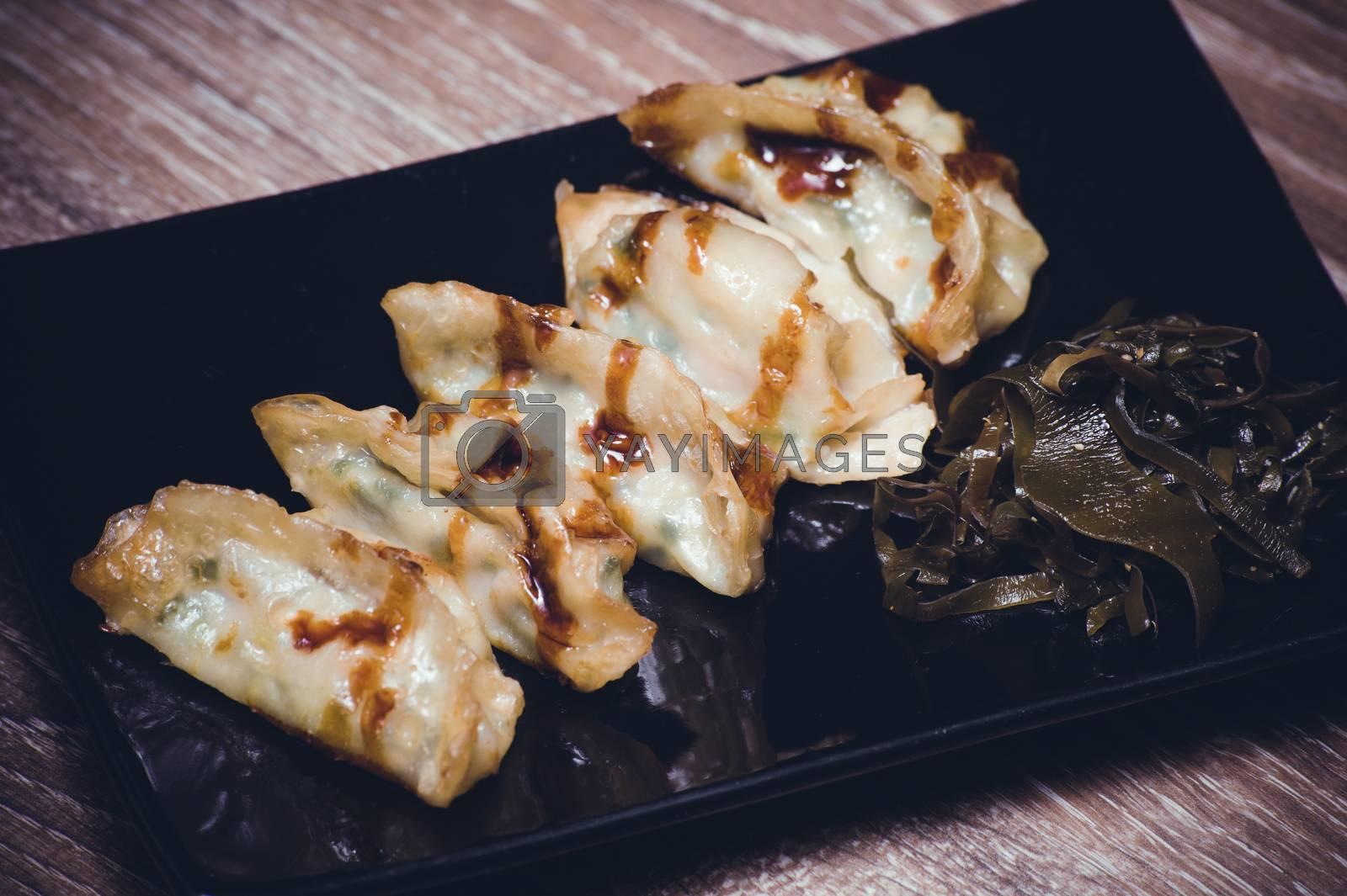 fried gyoza dumplings with sauce on black plate