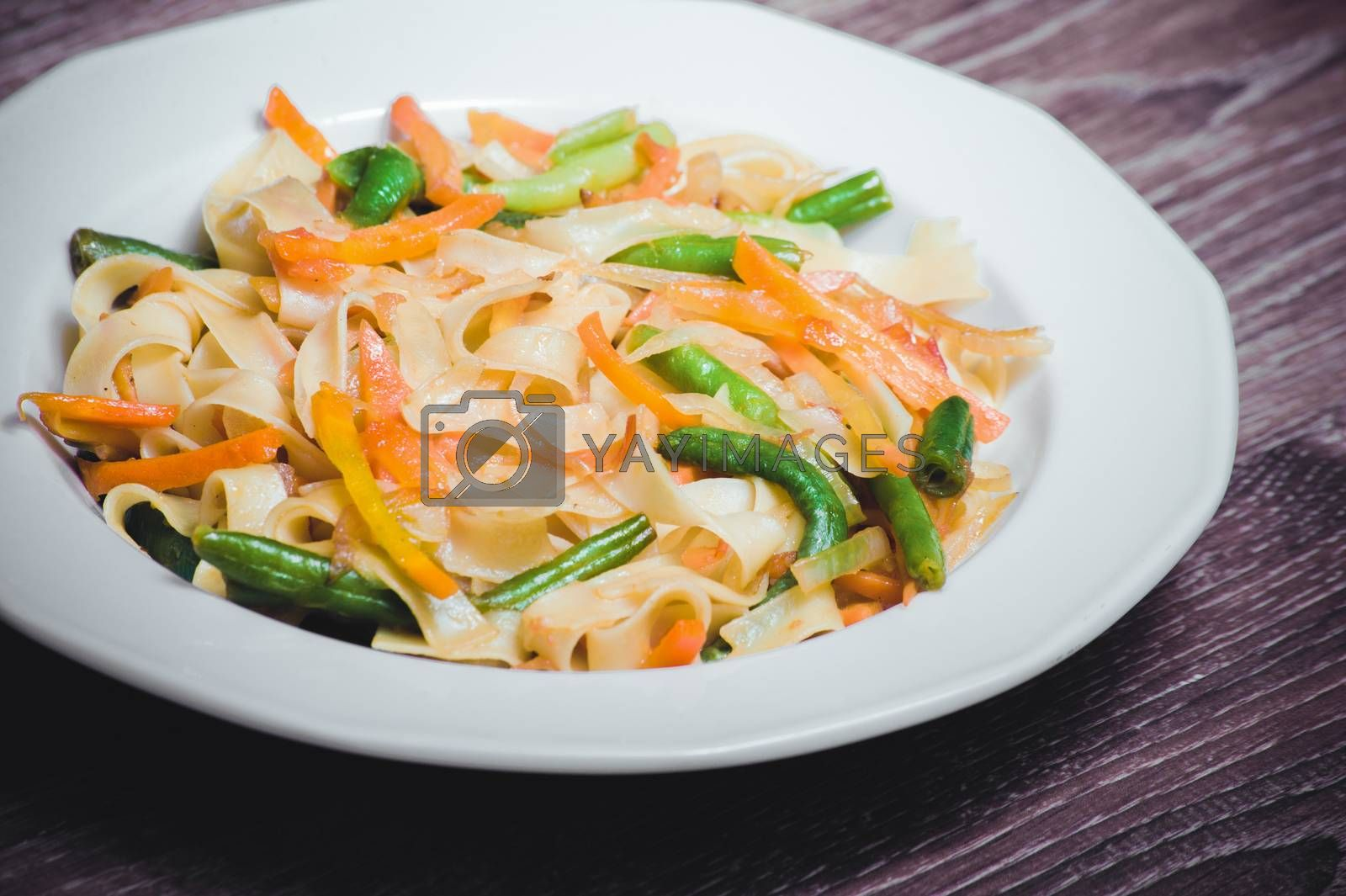 vegetarian pasta with carrot, zucchini on white plate