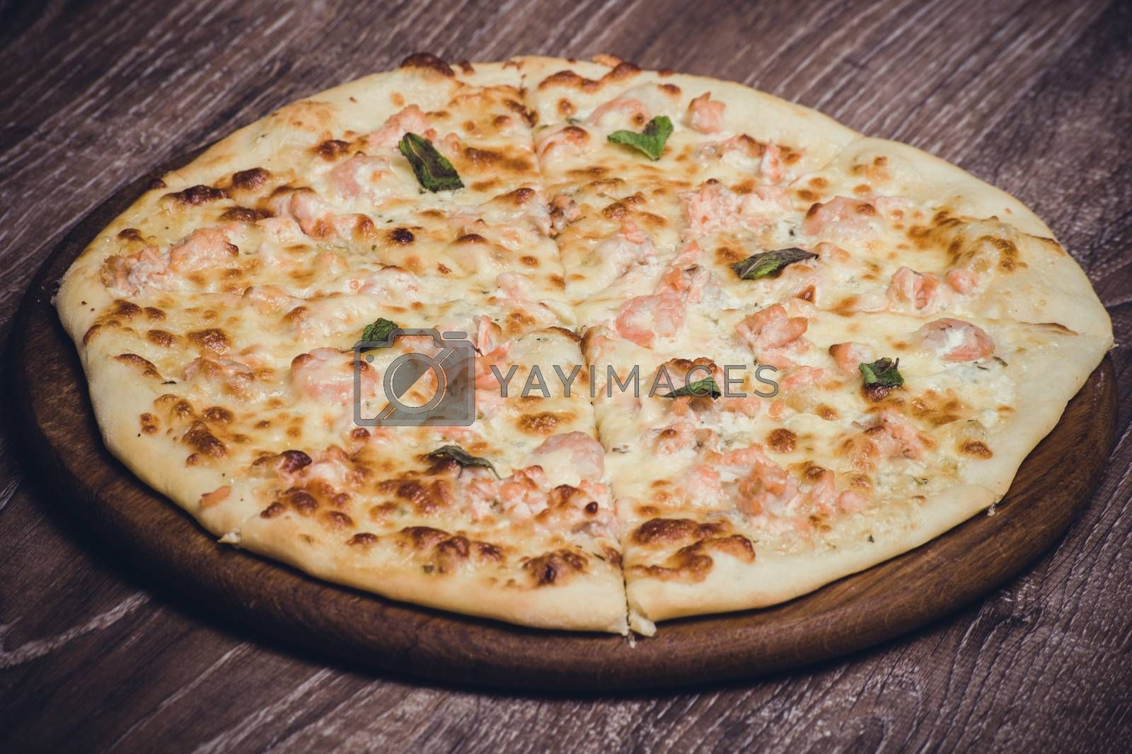 salmon and creamy sauce pizza on wooden board