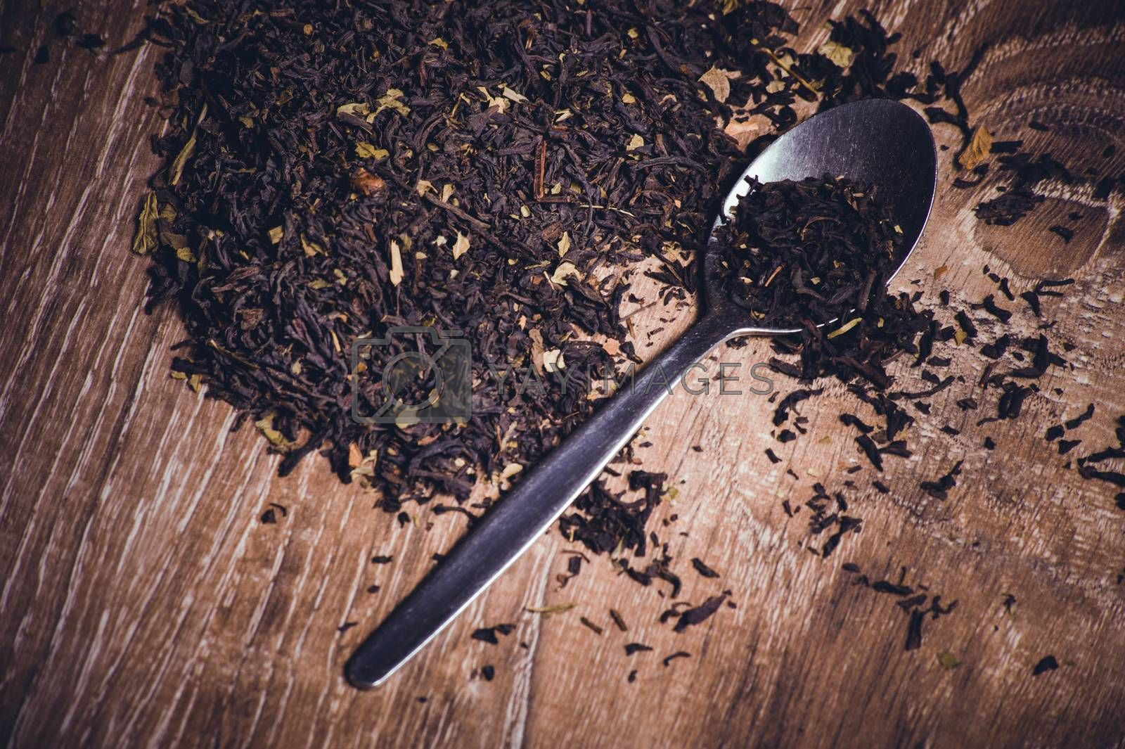 black tea dried leafs on spoon  on wooden background