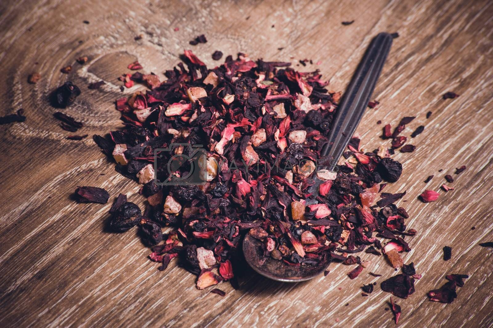 black tea leafs with fruits on spoon