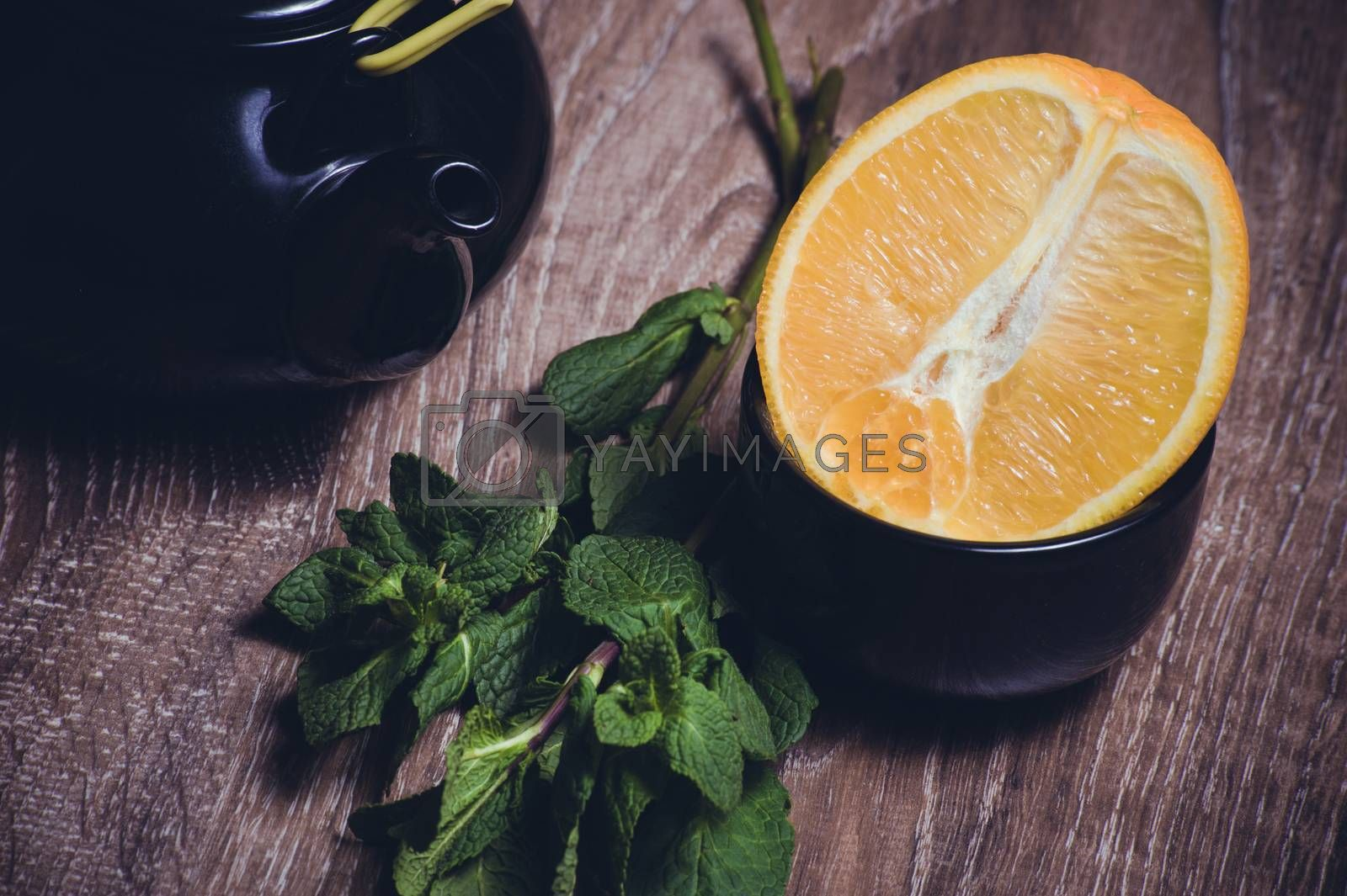 orange and mint tea served in cup and teapot