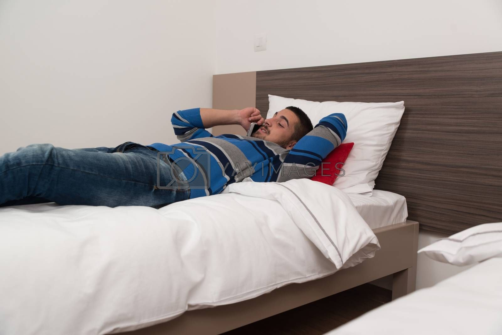 Young Man Lying On Bed And Having Fun On Phone In Bedroom