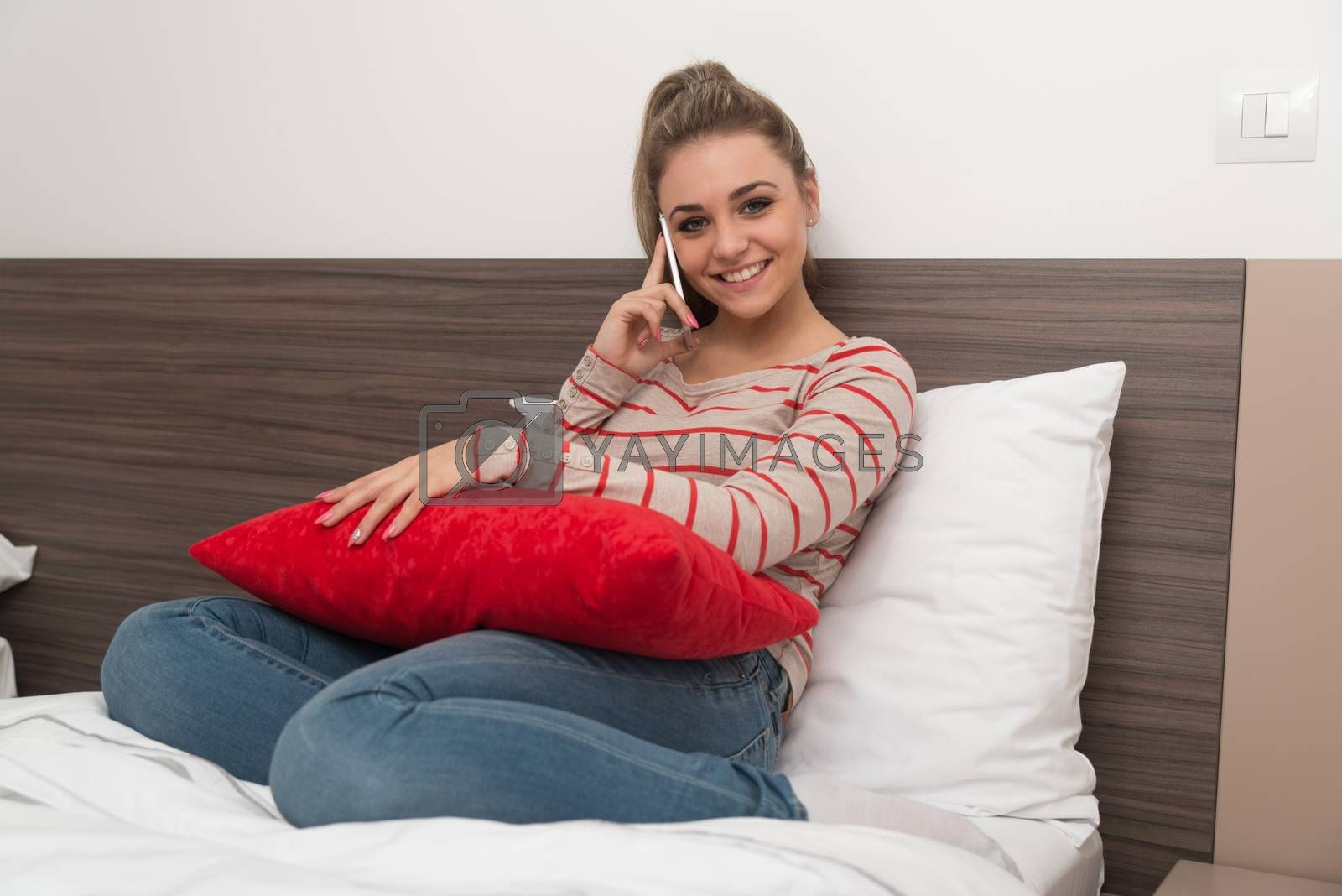 Young Woman Lying On Bed And Having Fun On Phone In Bedroom