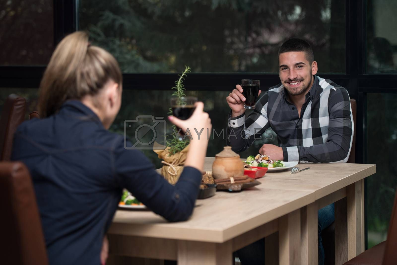 Royalty free image of Romantic Young Couple At Restaurant Table Toasting by JalePhoto