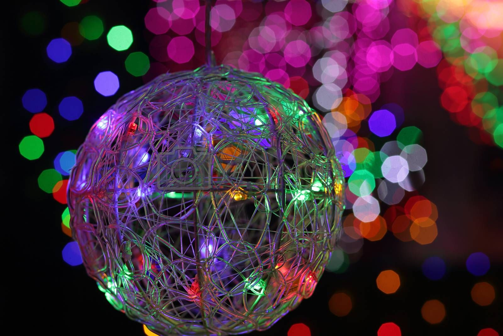 BEAUMONT HILLS, AUSTRALIA - DECEMBER 24, 2015;  Christmas wire mesh bauble ball in foreground with defocused colorued led lights in background - bokeh