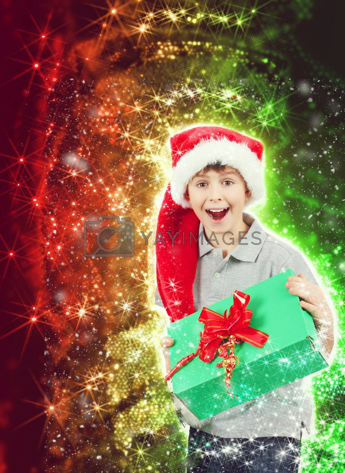surprised boy in santa hat with christmas present on abstract christmas background