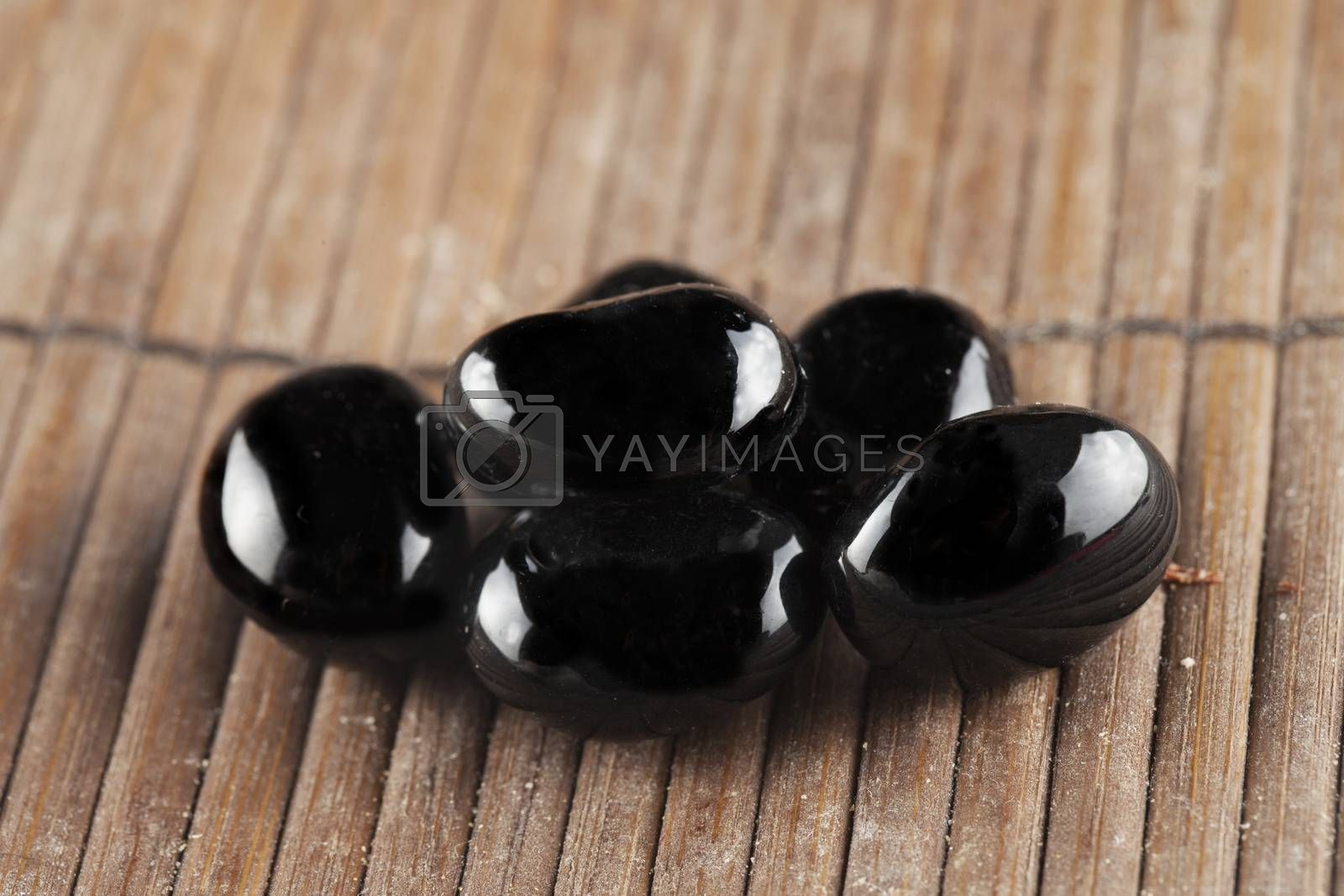 Black stones over wooden background, horizontal image