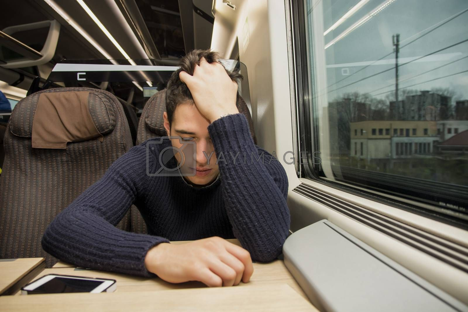 Bored tired young man traveling on a train sitting in a passenger coach with his head resting on his hand and eyes closed