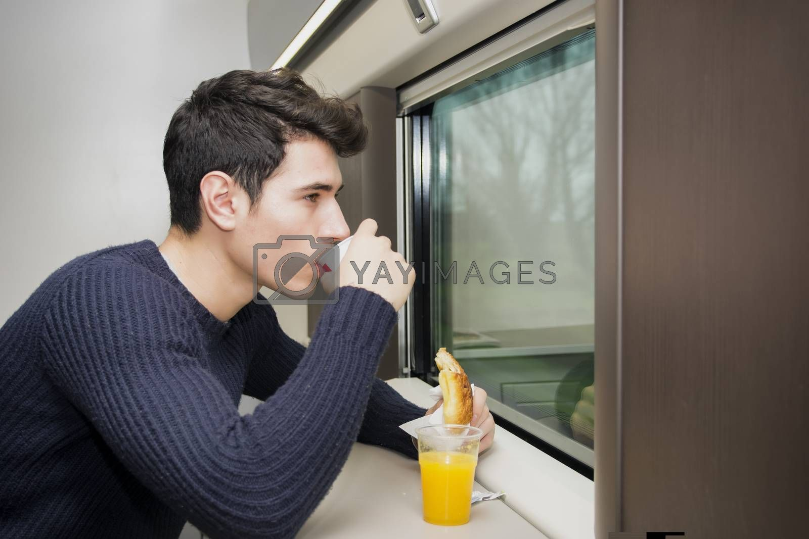 Young man eating refreshments on a train balancing the fruit juice on the ledge below the window as he eats a roll and coffee while commuting or traveling