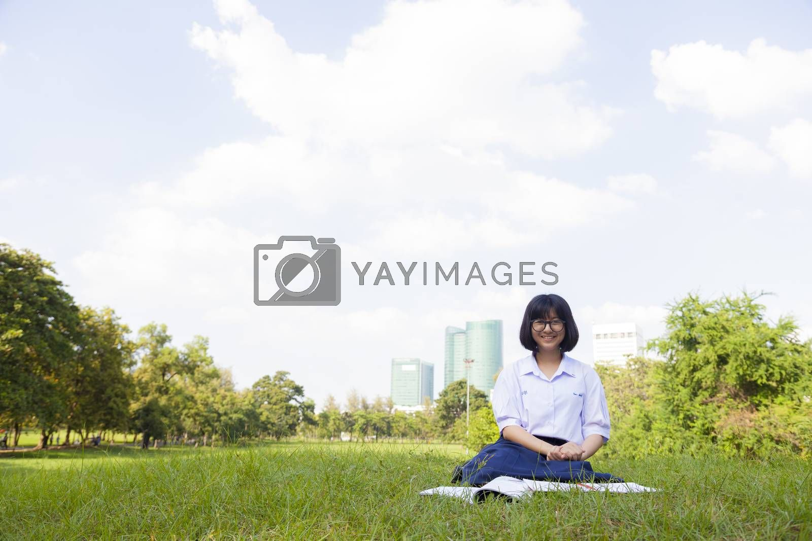 Girl sitting and smiling. On the lawn a happy and relaxation. On a clear sunny sky.