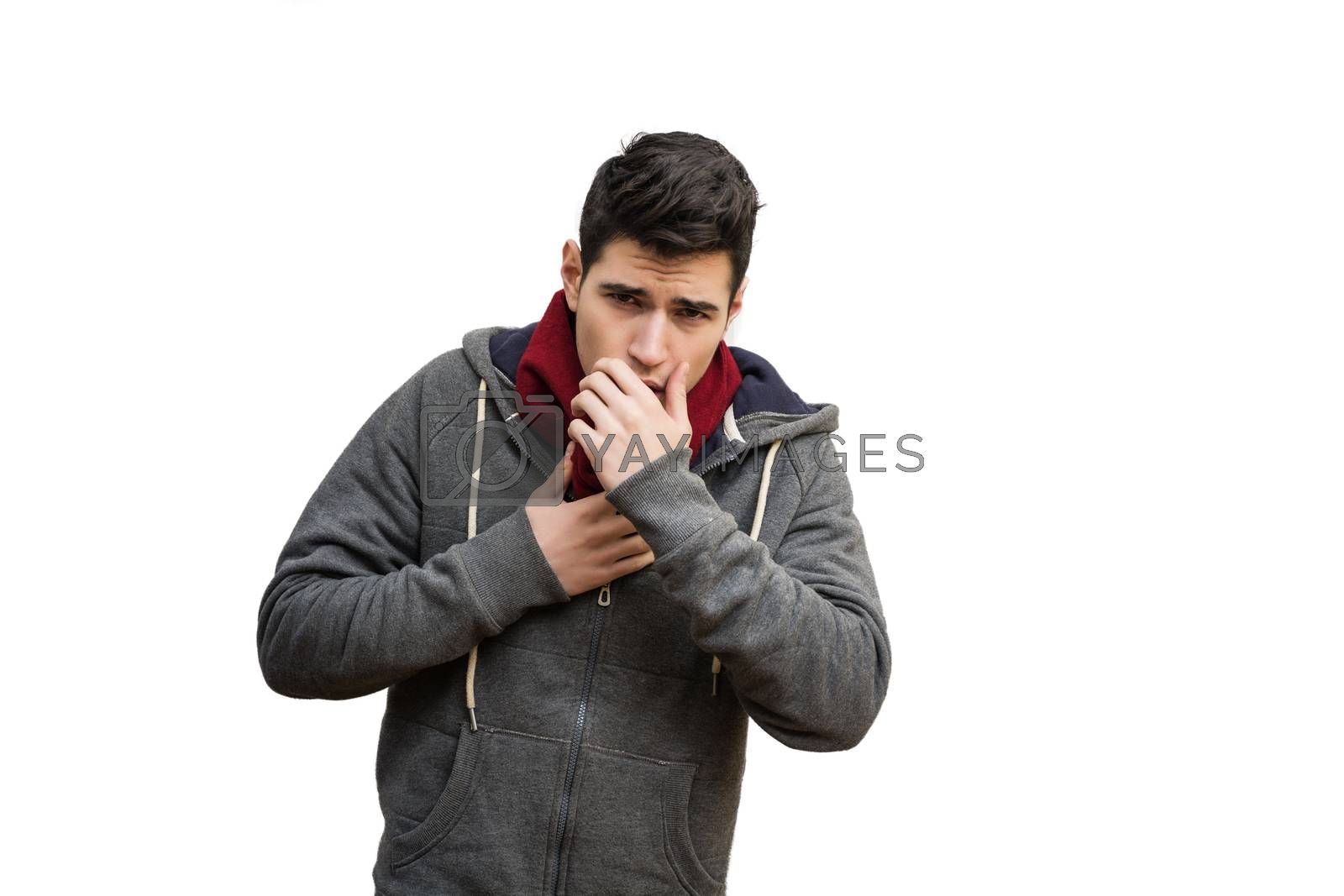 Young man sick with flu or cold, coughing with hand in front of his mouth, isolated on white