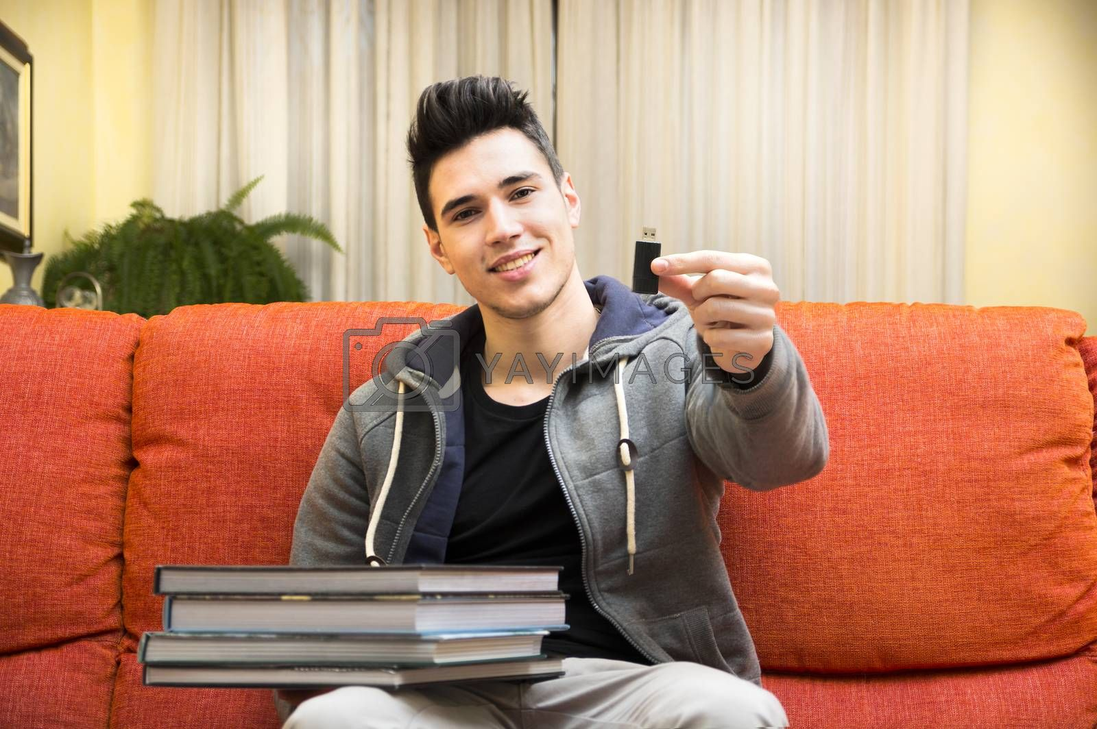 Smiling young man showing difference between light and handy USB key in one hand and heavy books on other hand