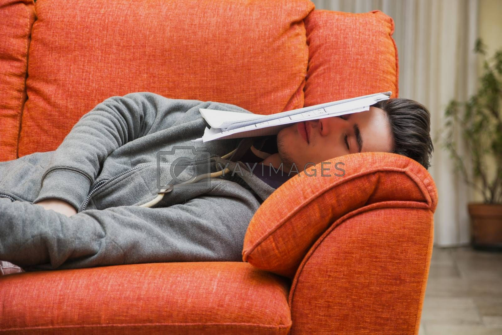 Over-worked, tired young man at home sleeping instead of working or studying, resting with head covered by paper sheets