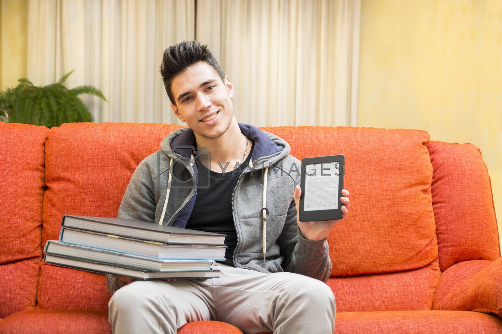 Smiling young man showing difference between light and handy ebook reader in one hand and heavy books on other hand