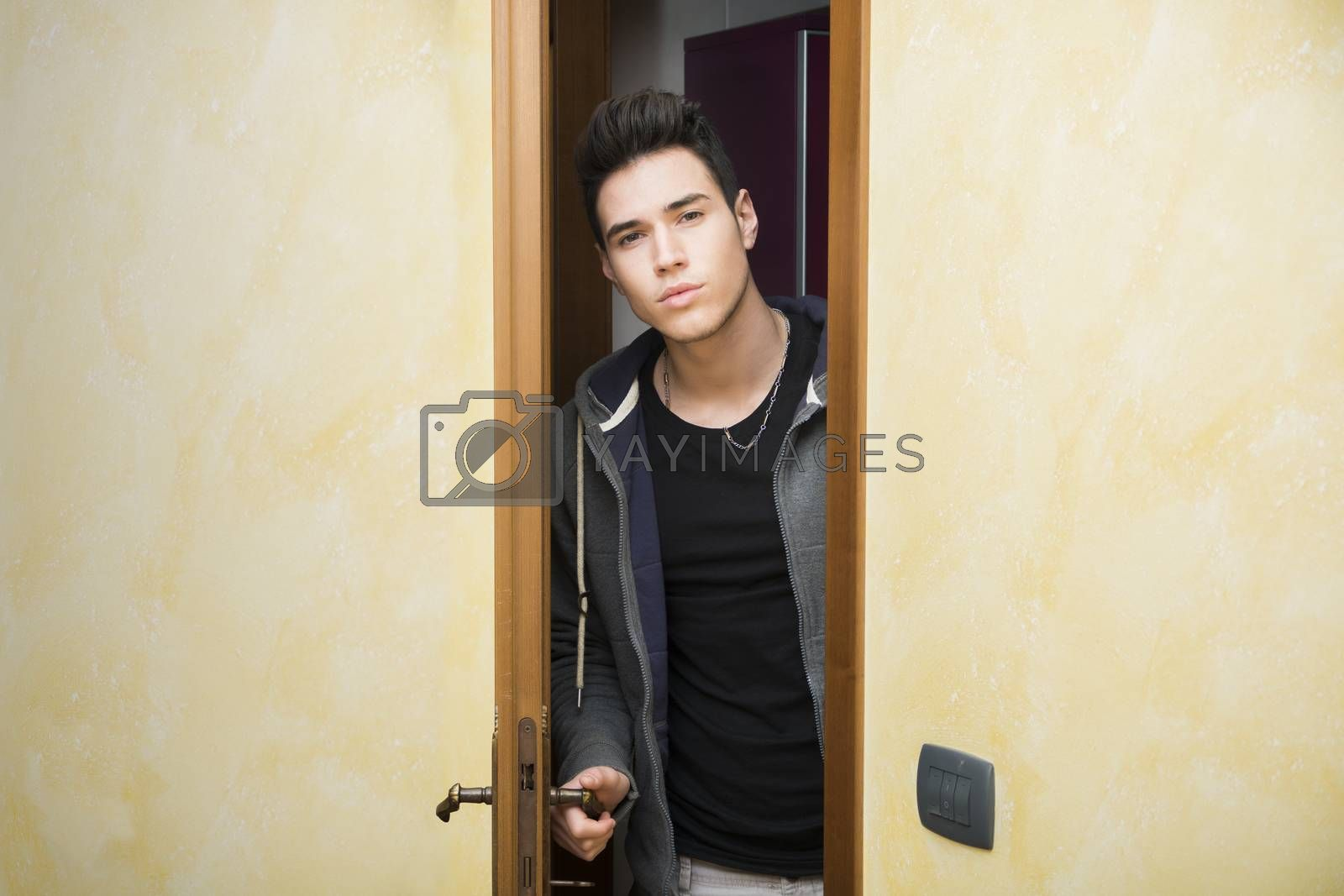 Handsome young man opening door to enter into a room, looking at camera