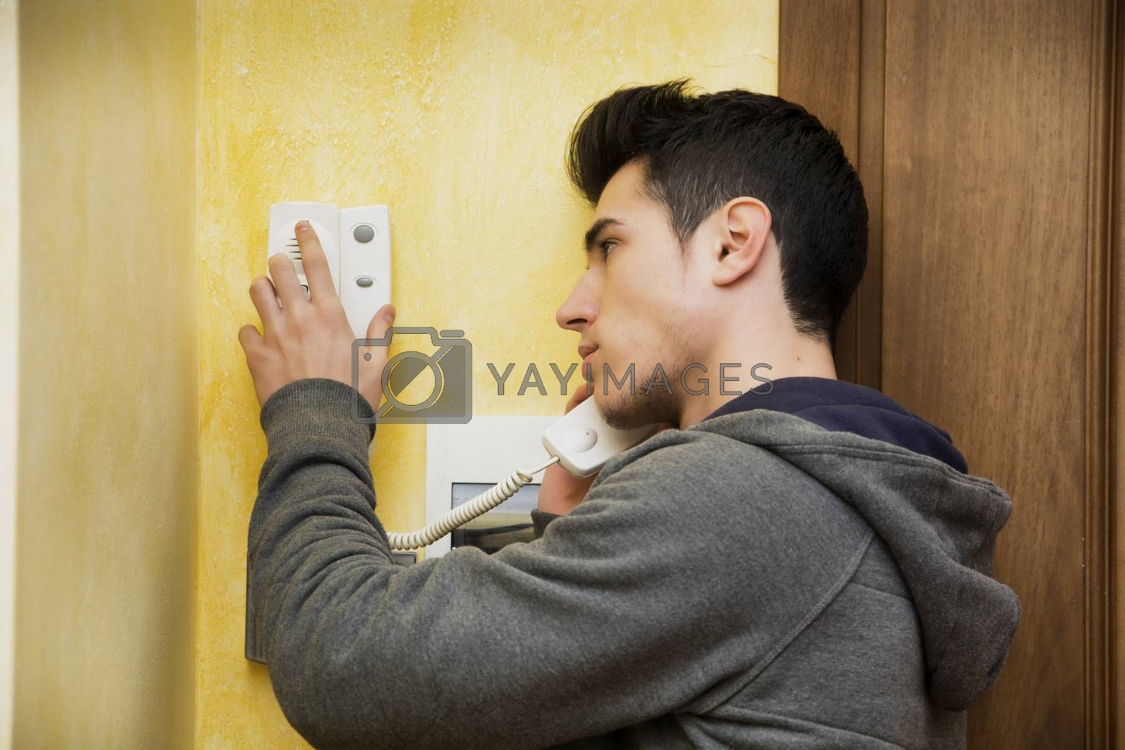 Teenager or young man answering the intercom in an apartment, pressing button to open entrance door