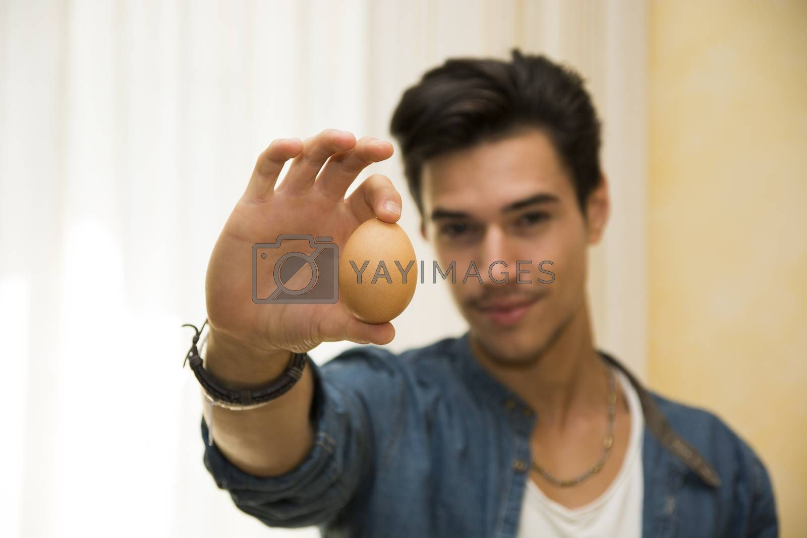 Smiling young man holding an egg in his hand, showing it to the camera