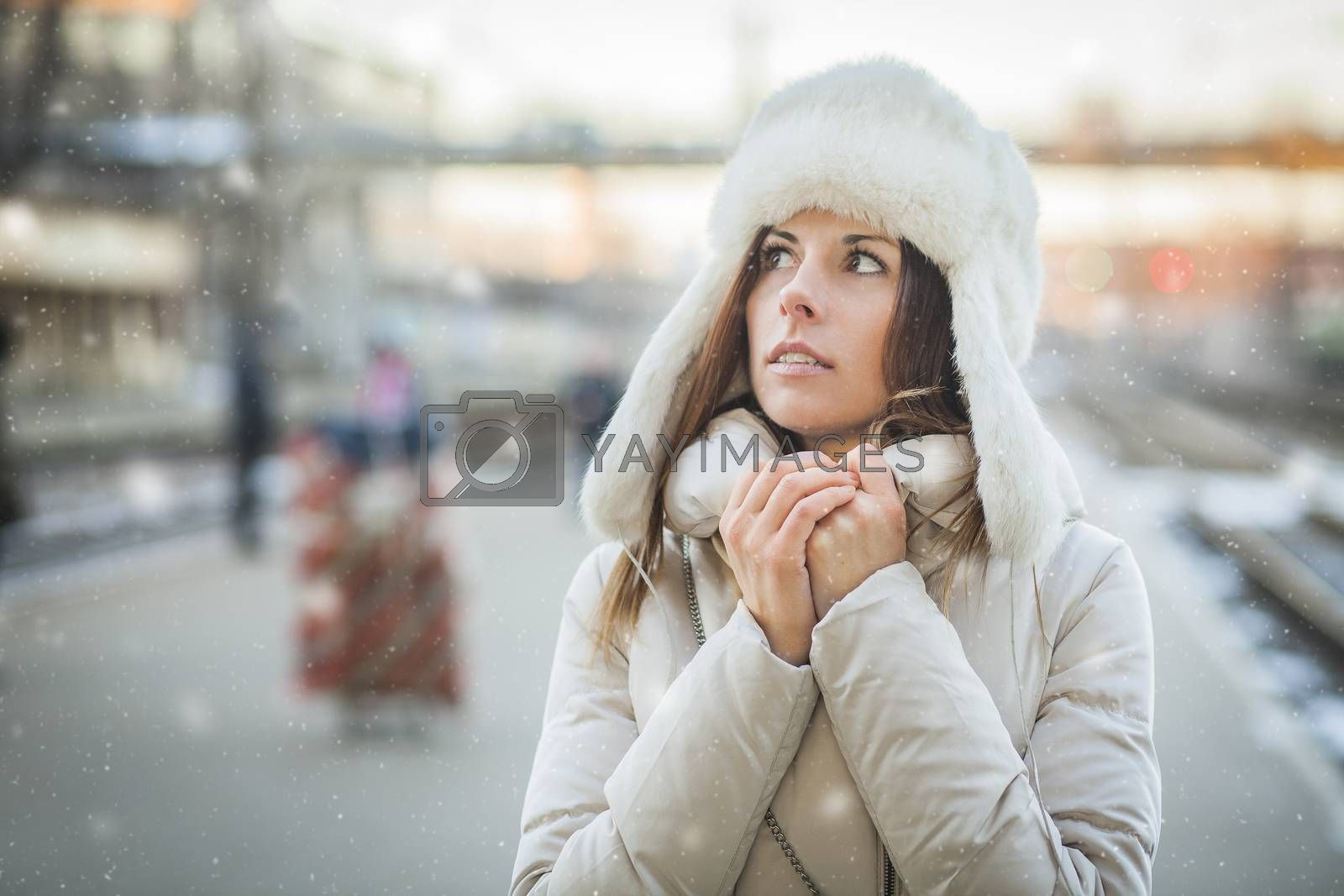 Girl is trying to warm up on a railroad station in snowy day