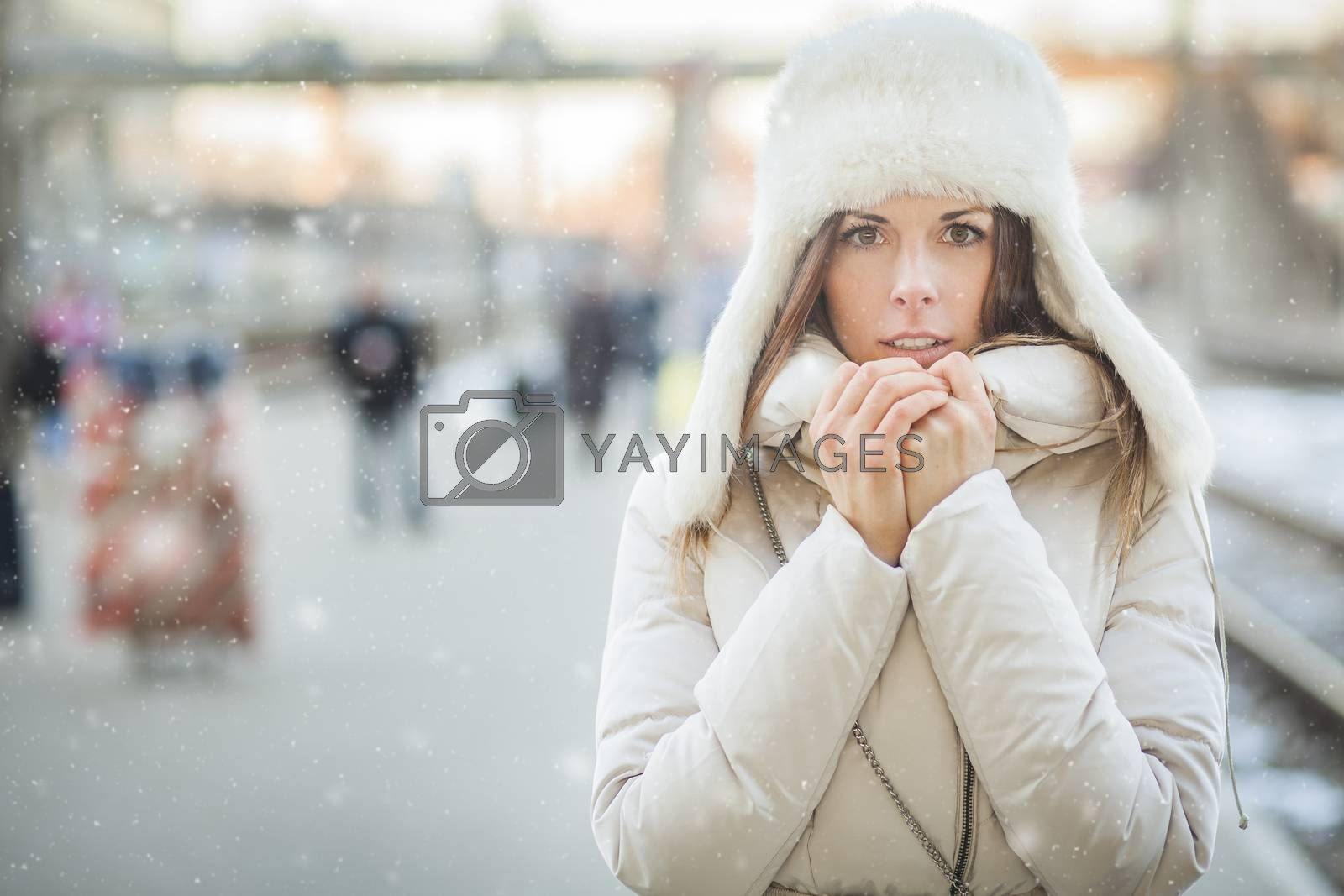 Girl freezing on a railroad platform in falling snow