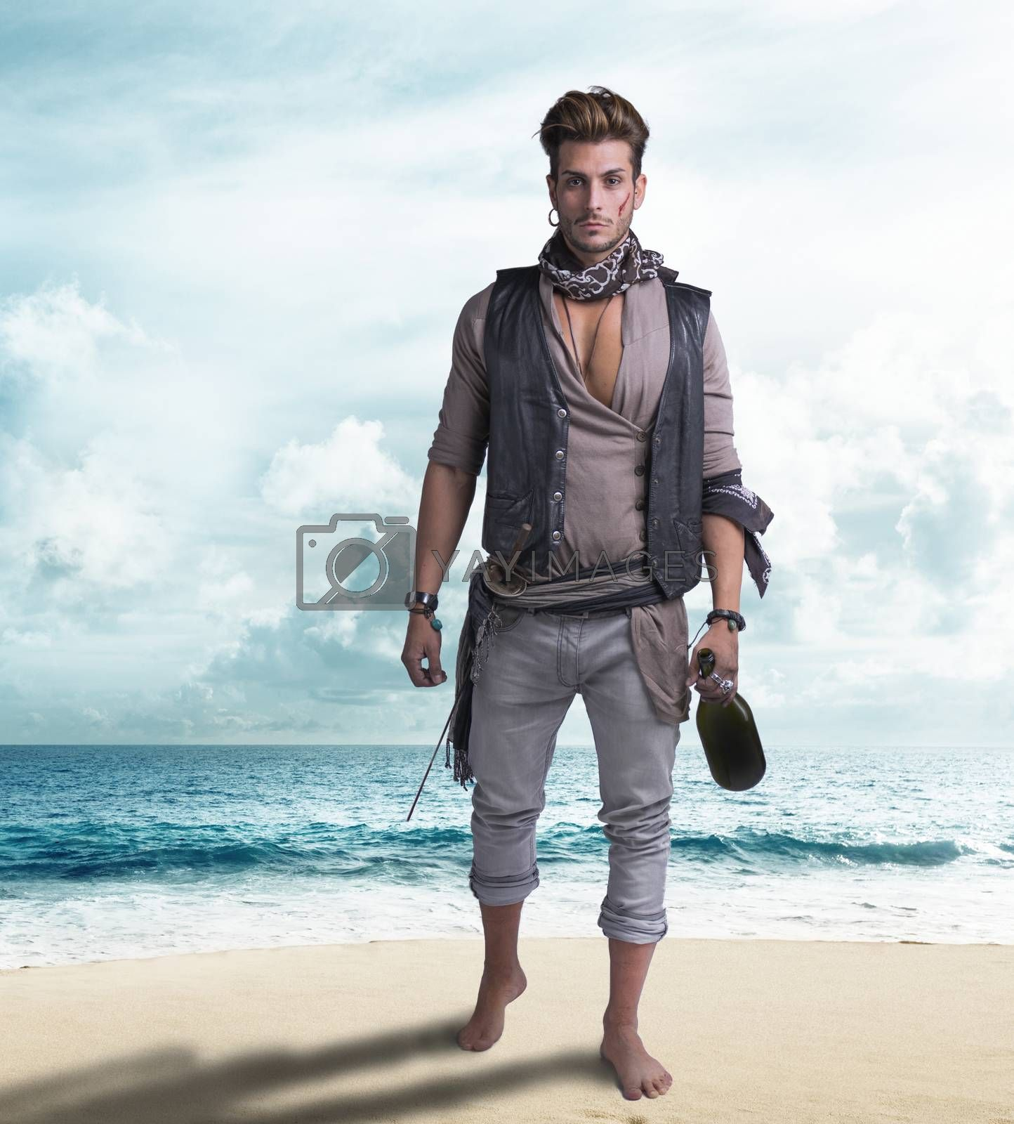Handsome young pirate on the beach, barefoot, holding wine bottle, looking at camera