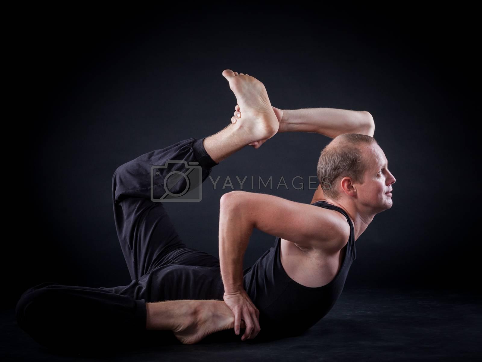 Handsome man doing yoga. Shot on black background