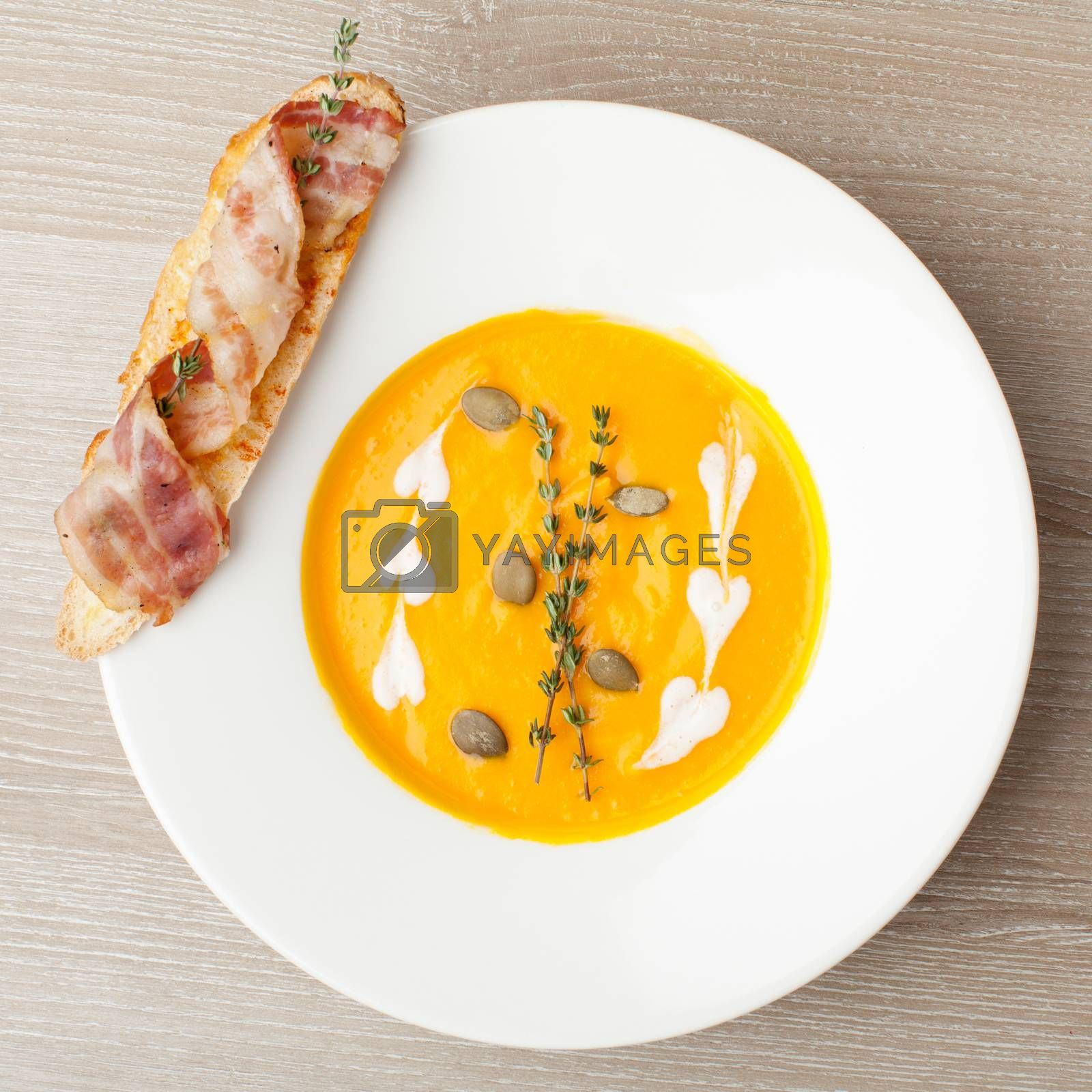 Pumpkin cream soup puree with ginger smack,  served in white plate , baked bread slice, bacon, seeds and  thyme
