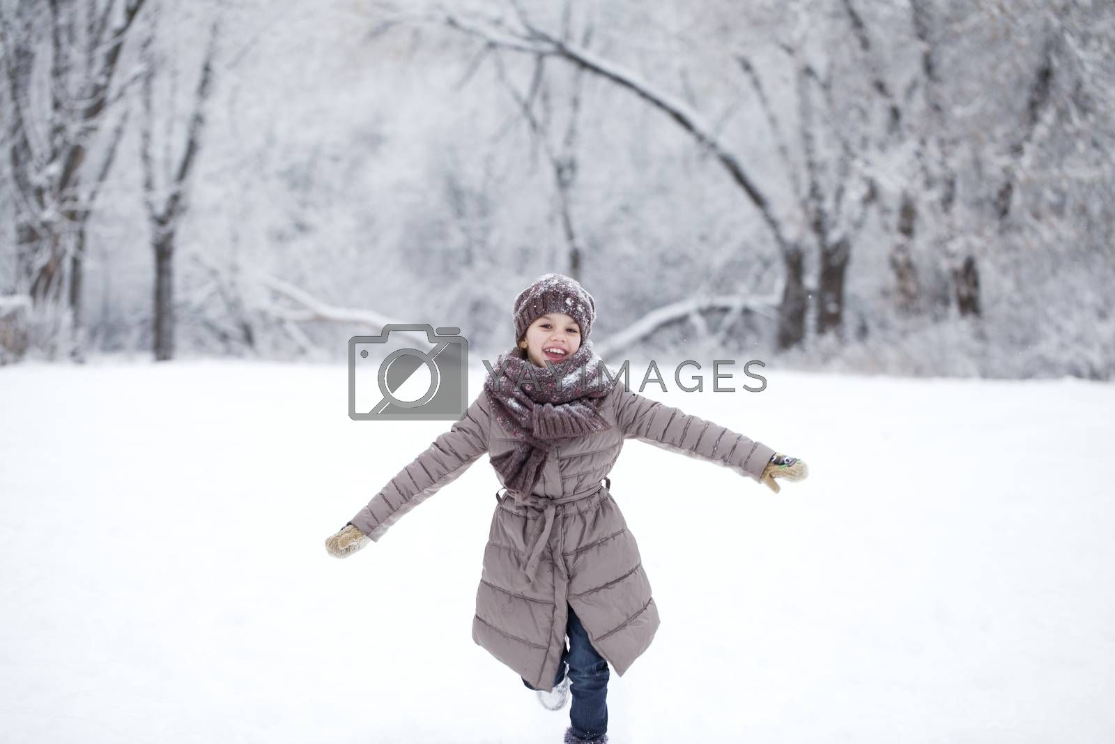 Little girl running on the background of snow covered winter park