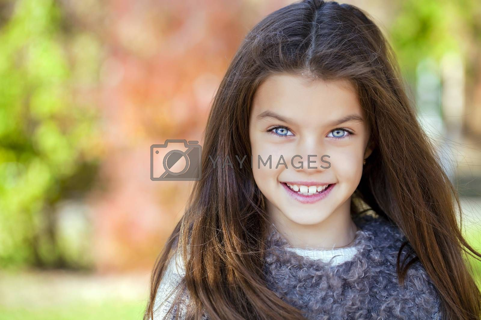 Close up portrait of a beautiful nine year old little girl in autumn park