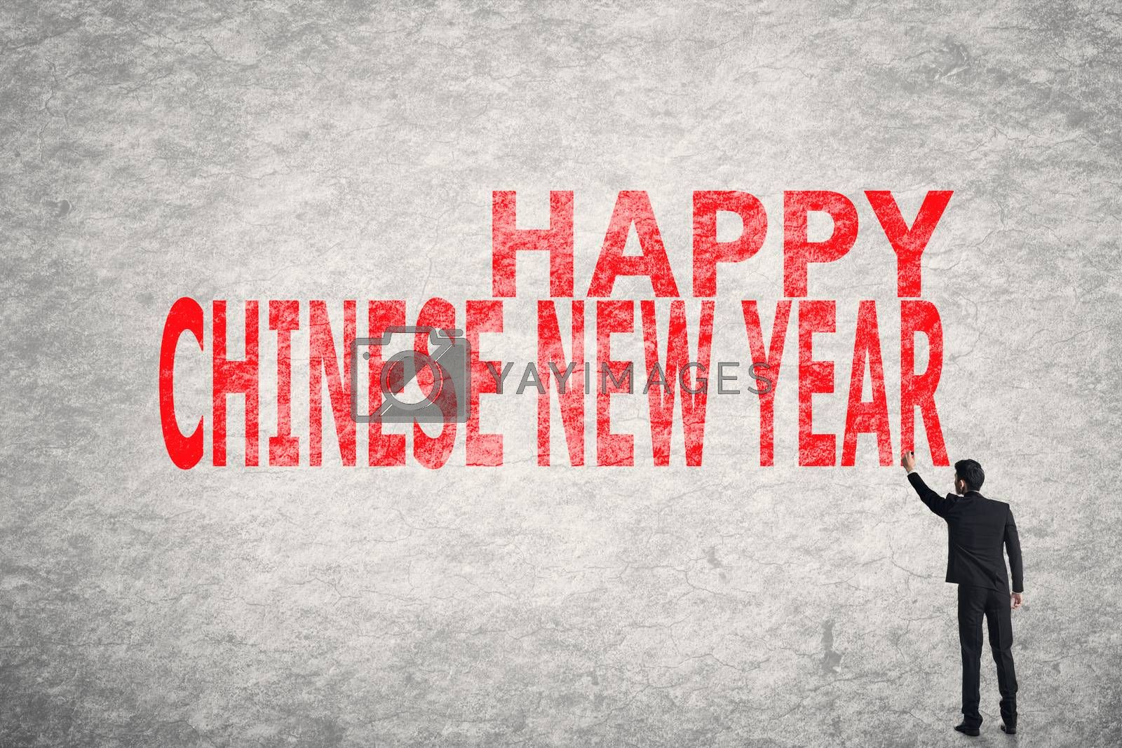 Asian businessman write text on wall, Happy Chinese New Year