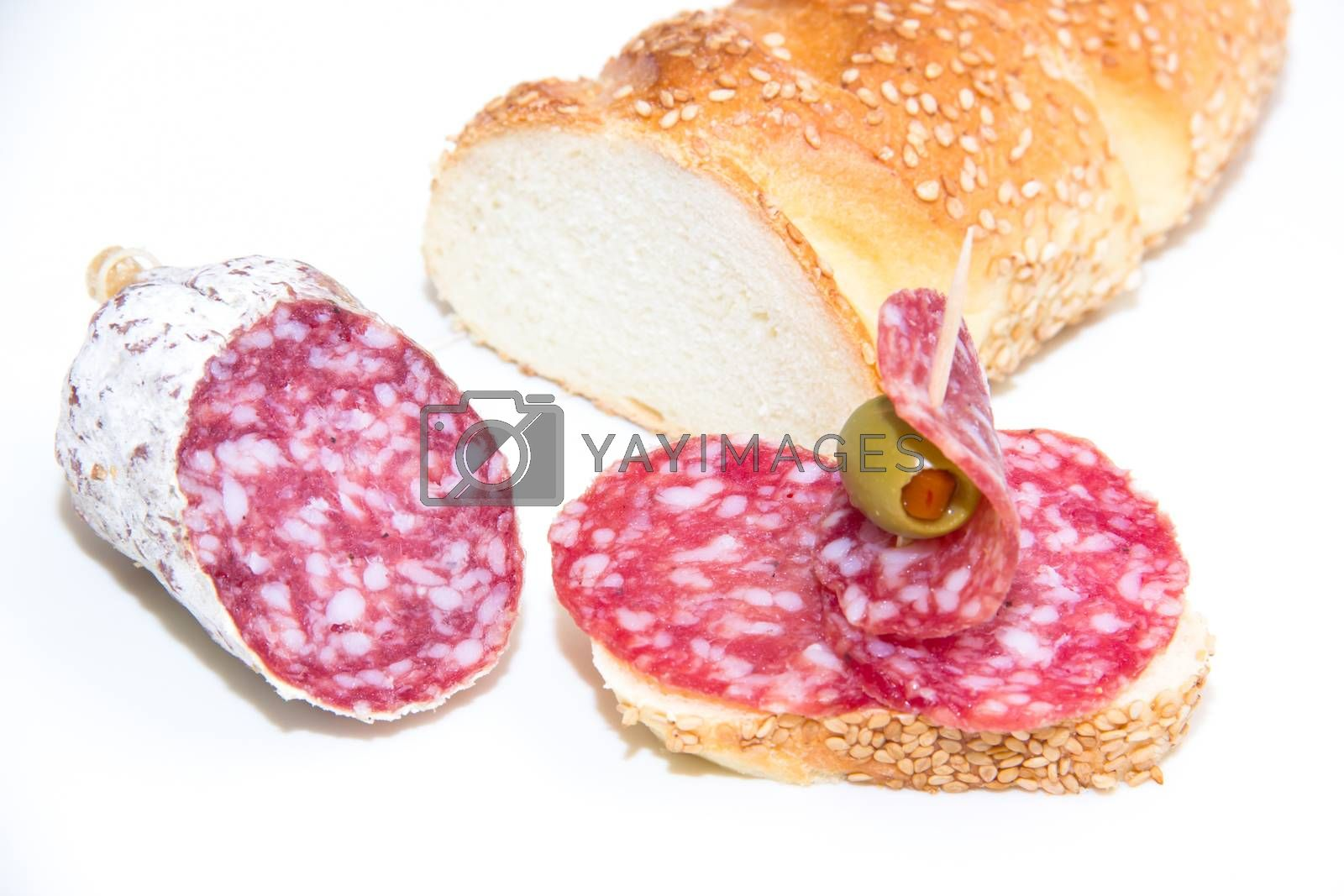 Bread with slices of salami on white background