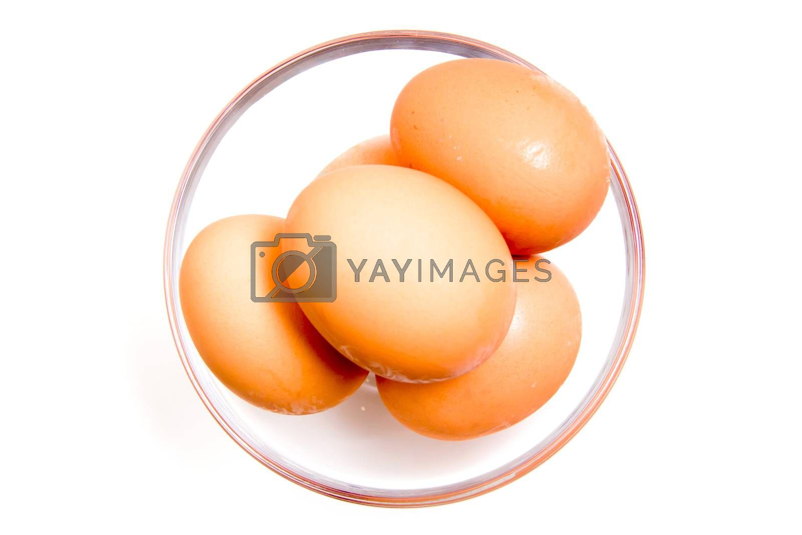 Eggs in glass bowl on white background from above
