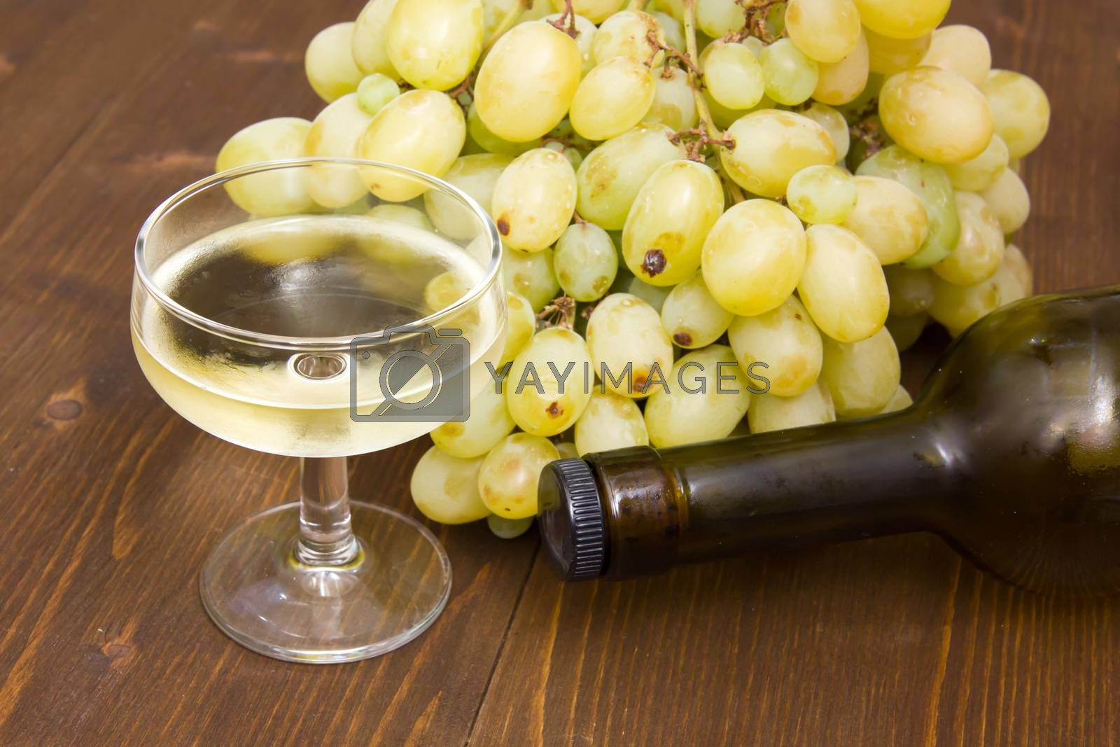 Glass of wine with grapes and bottle on wooden table